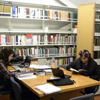 2 mujeres leyendo en una habitación, al fondo se pueden ver repisas repletas de libros