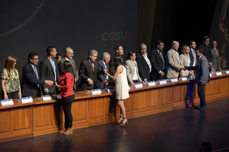 Estudiantes sobresalientes de la Universidad de Guadalajara, recibiendo reconocimiento de manos de las autoridades universitarias