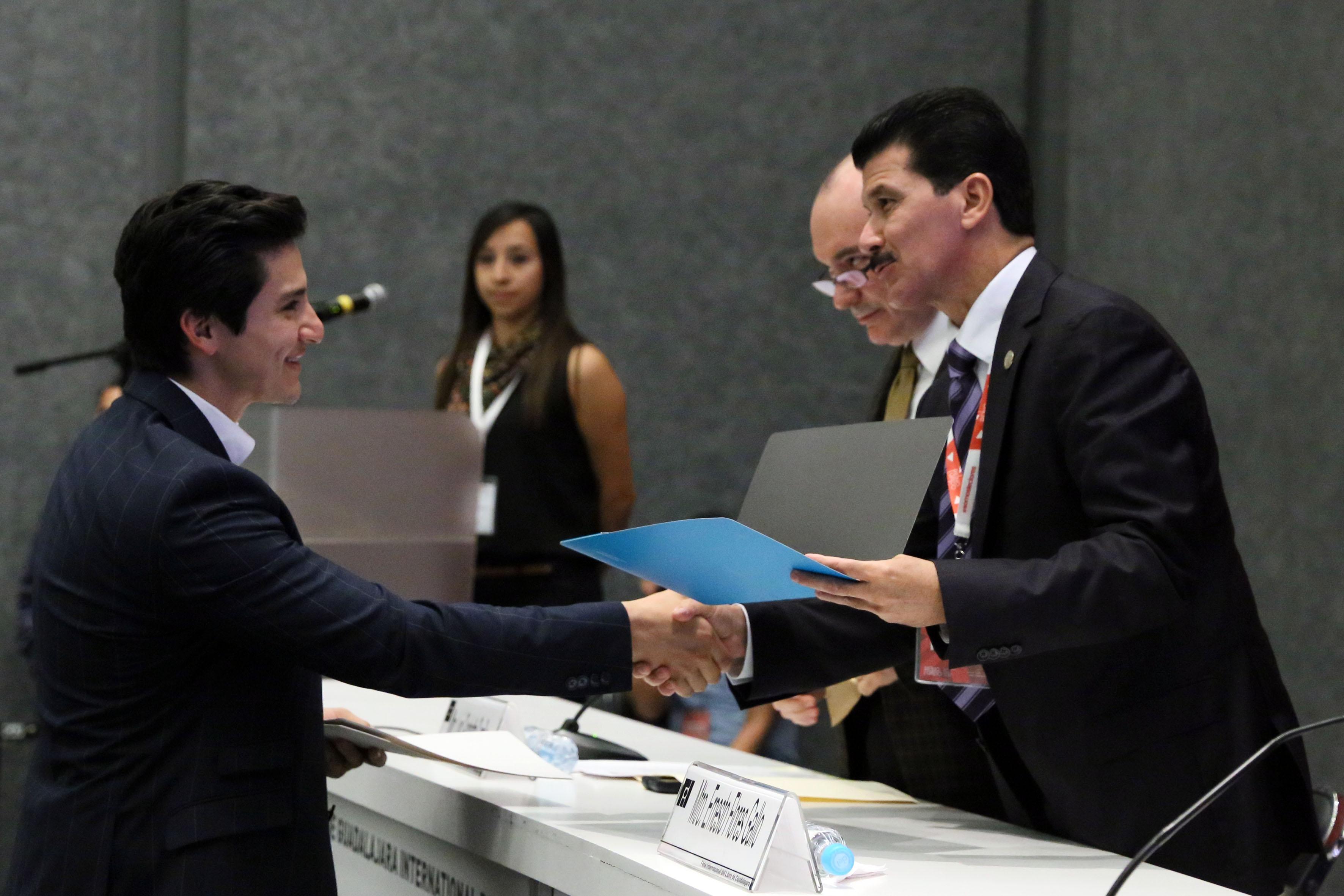 Rector del Centro Universitario de Arte, Arquitectura y Diseño (CUAAD), maestro Ernesto Flores Gallo, haciendo entrega del reconocimiento al jóven arquitecto ganador del concurso.