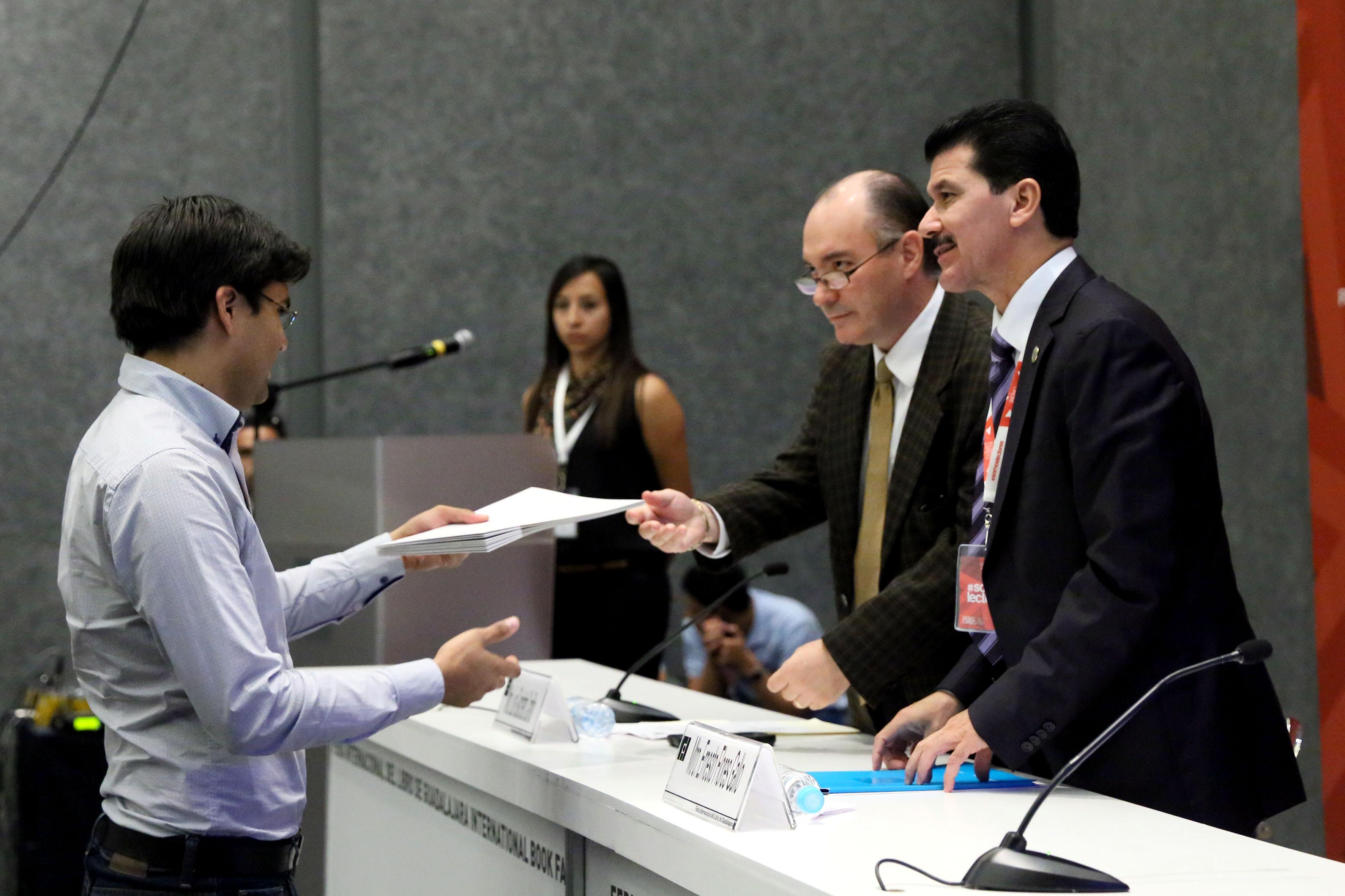 Mtro. Luis Giachetto Carrillo, haciendo entrega de reconocimiento a jóven arquitecto ganador del concurso.