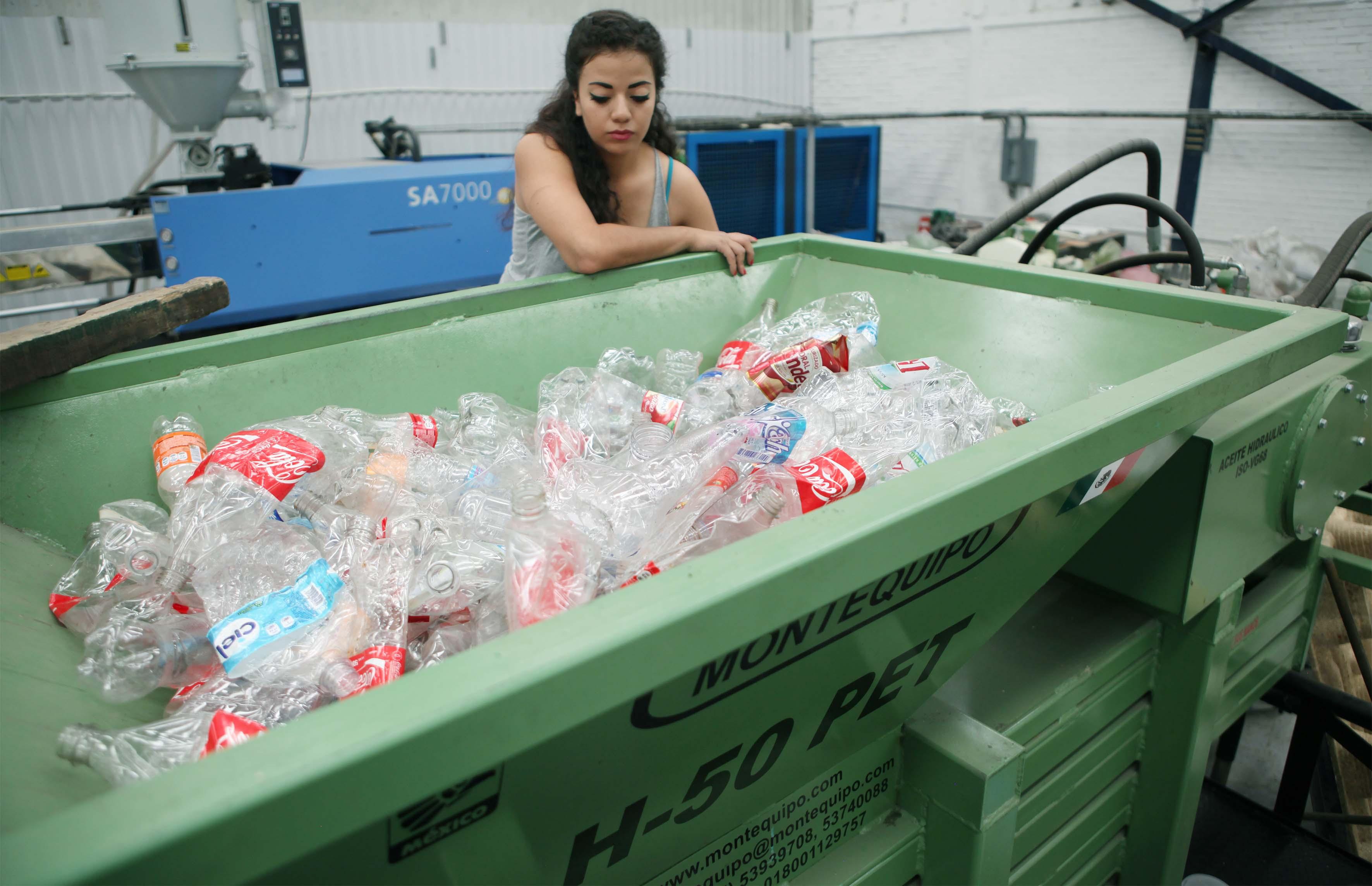 Mujer junto a contenedor lleno de botellas de plastico
