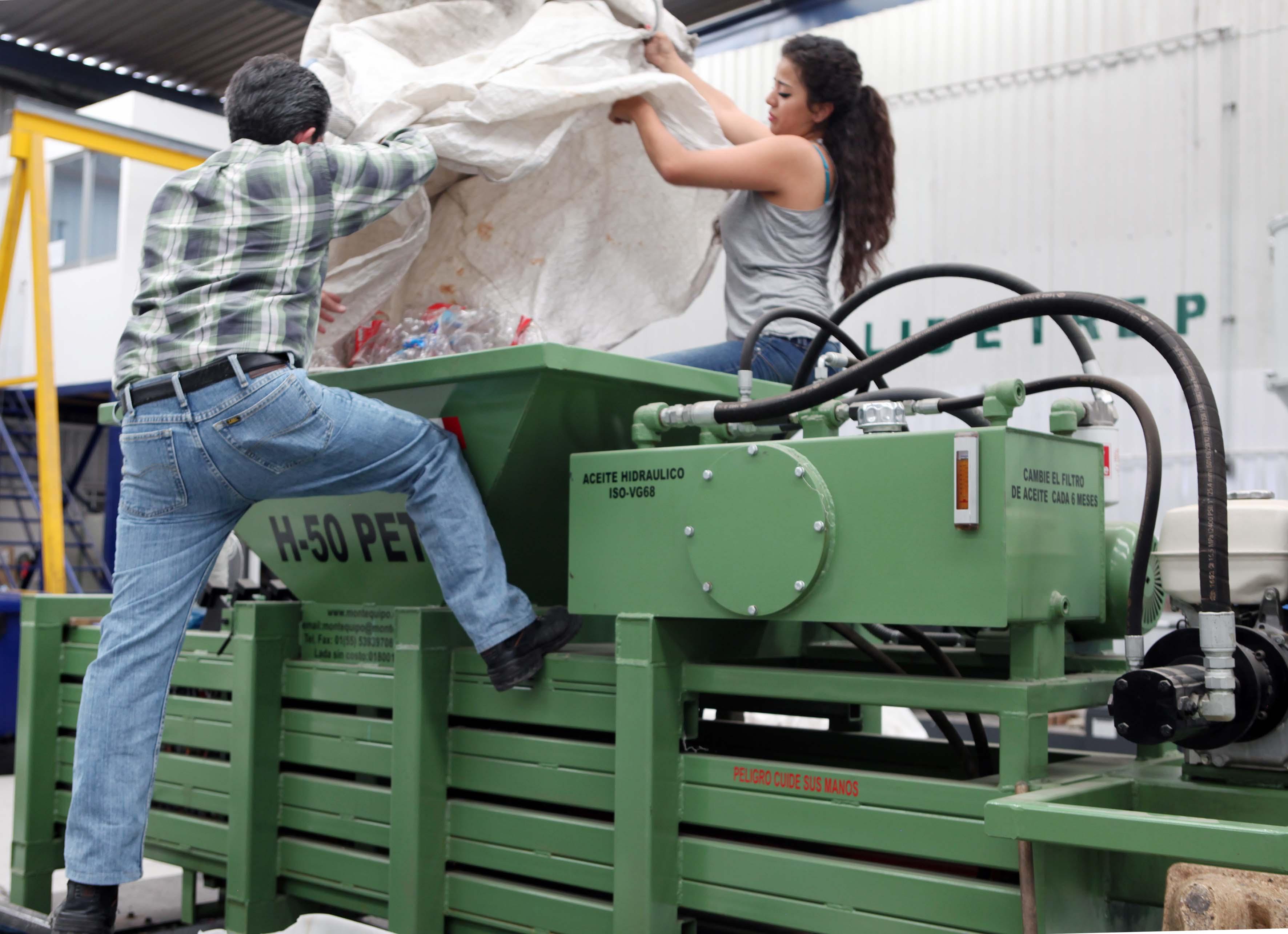 Hombre y mujer depositando botellas de plástico en maquina de reciclado