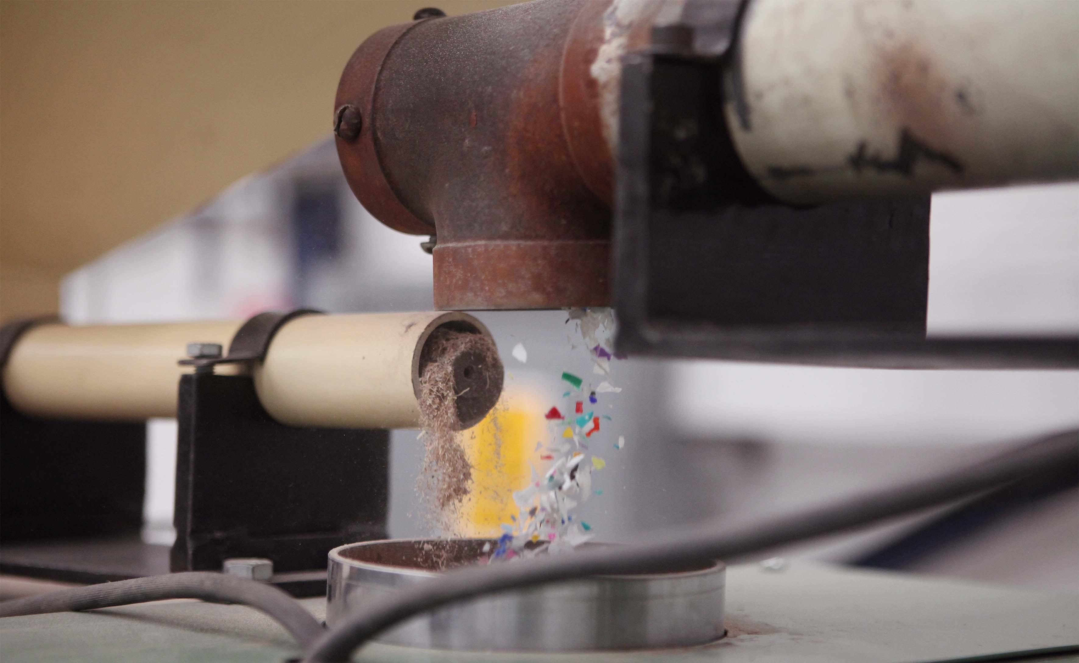 Material plastico saliendo de una maquina, ya triturado