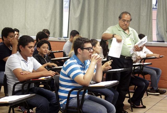 Aplicador entregando exámenes a estudiantes
