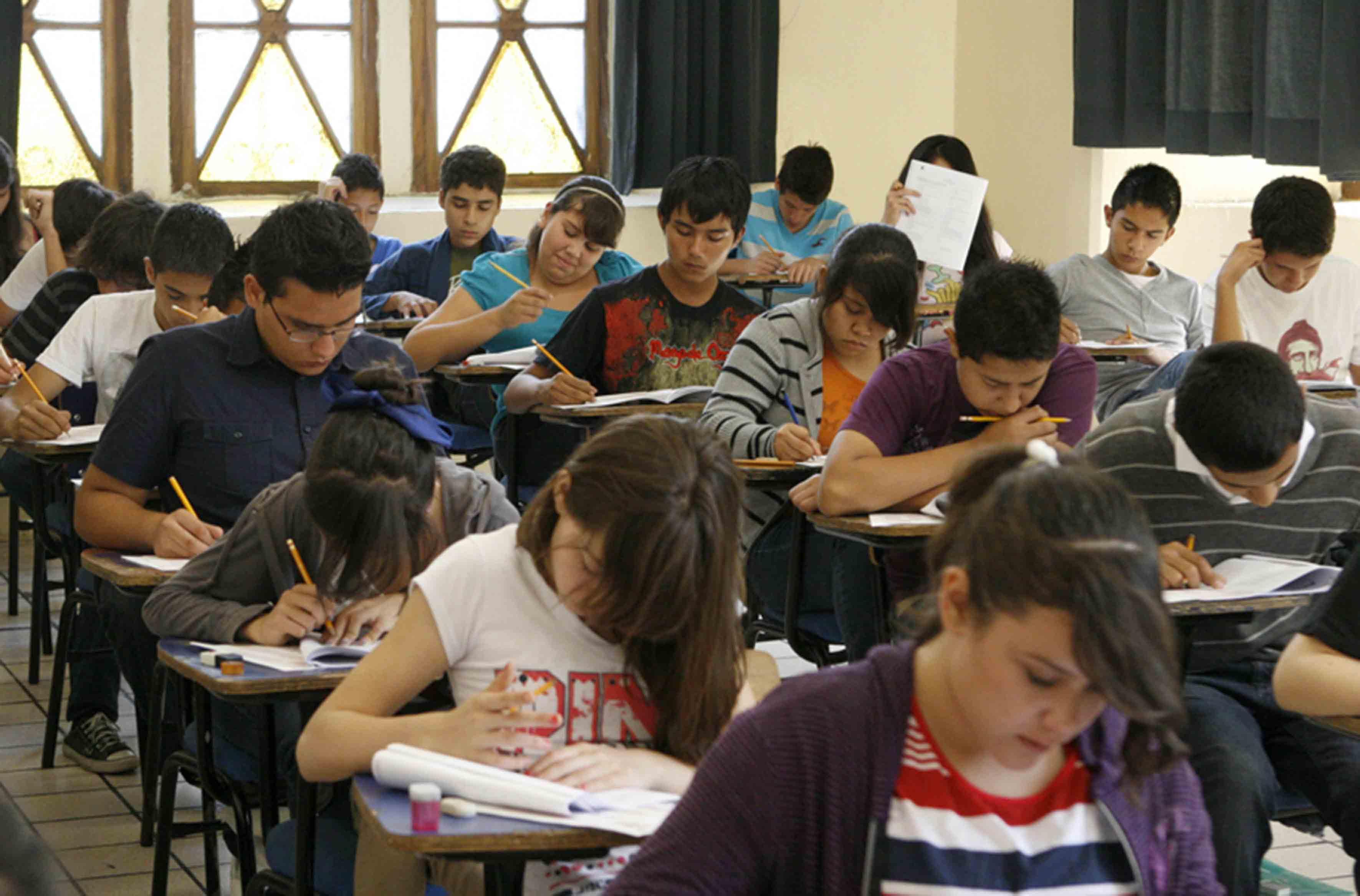 Jóvenes aspirantes a preparatoria realizando examen de admisión.
