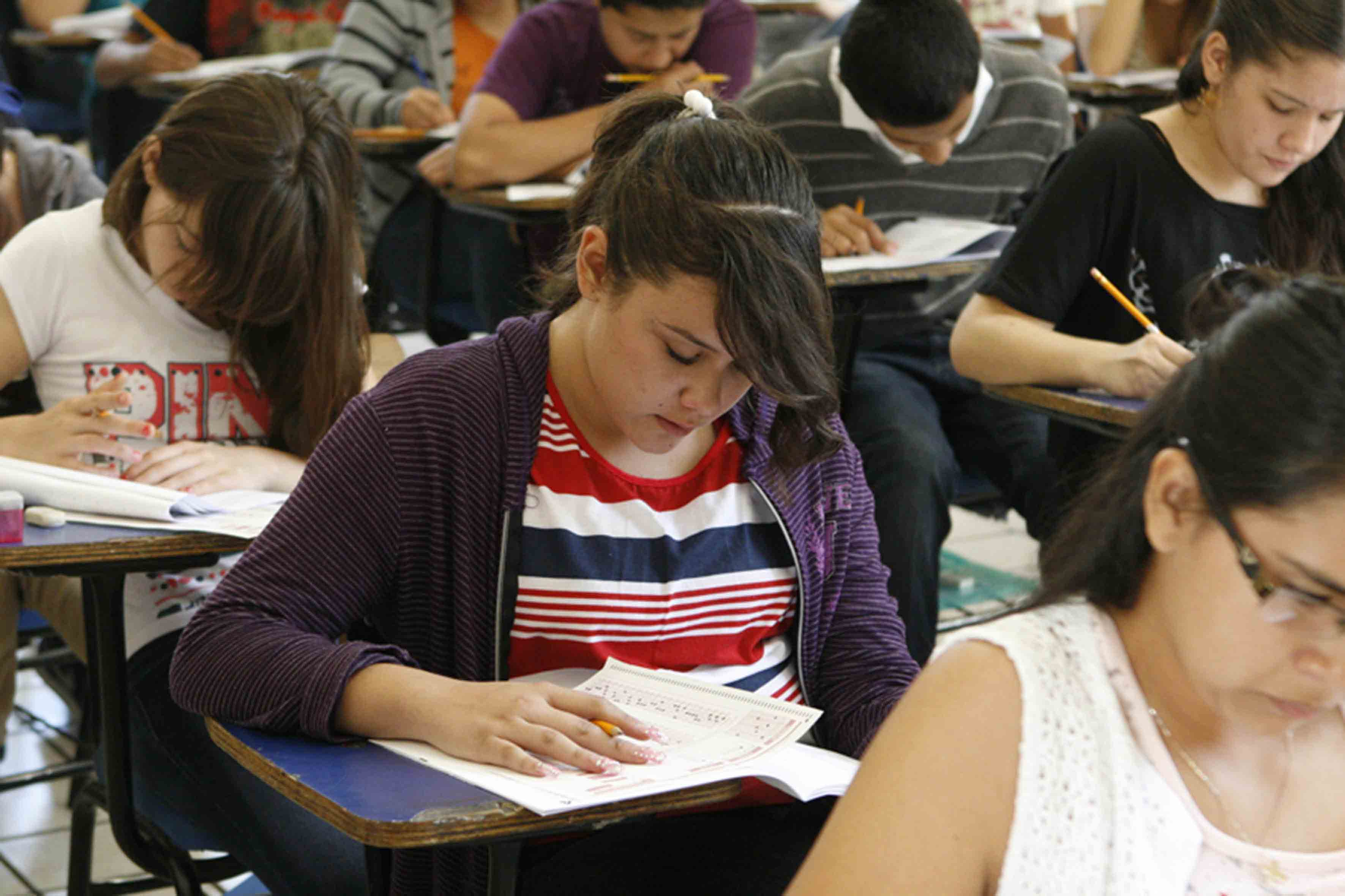 Jóvenes realizando examen de admisión a preparatorias universitarias