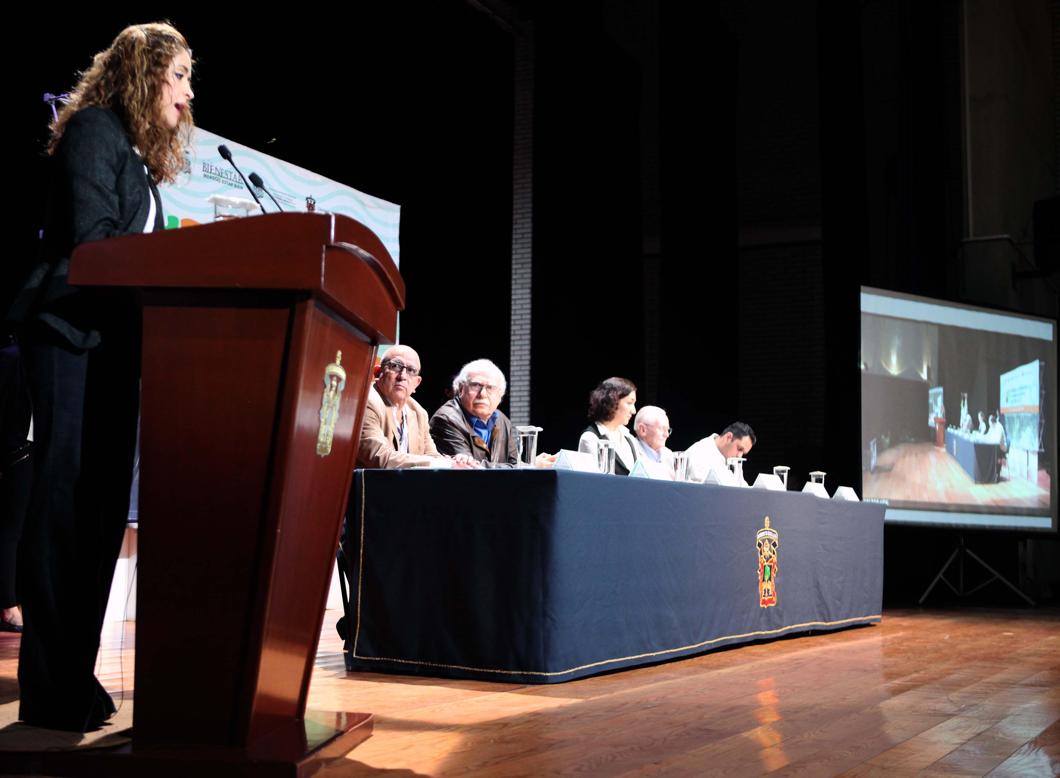 """Mujer en el podio, participando  en la conferencia """"Ordenación del territorio como ejercicio científico y acción política"""""""
