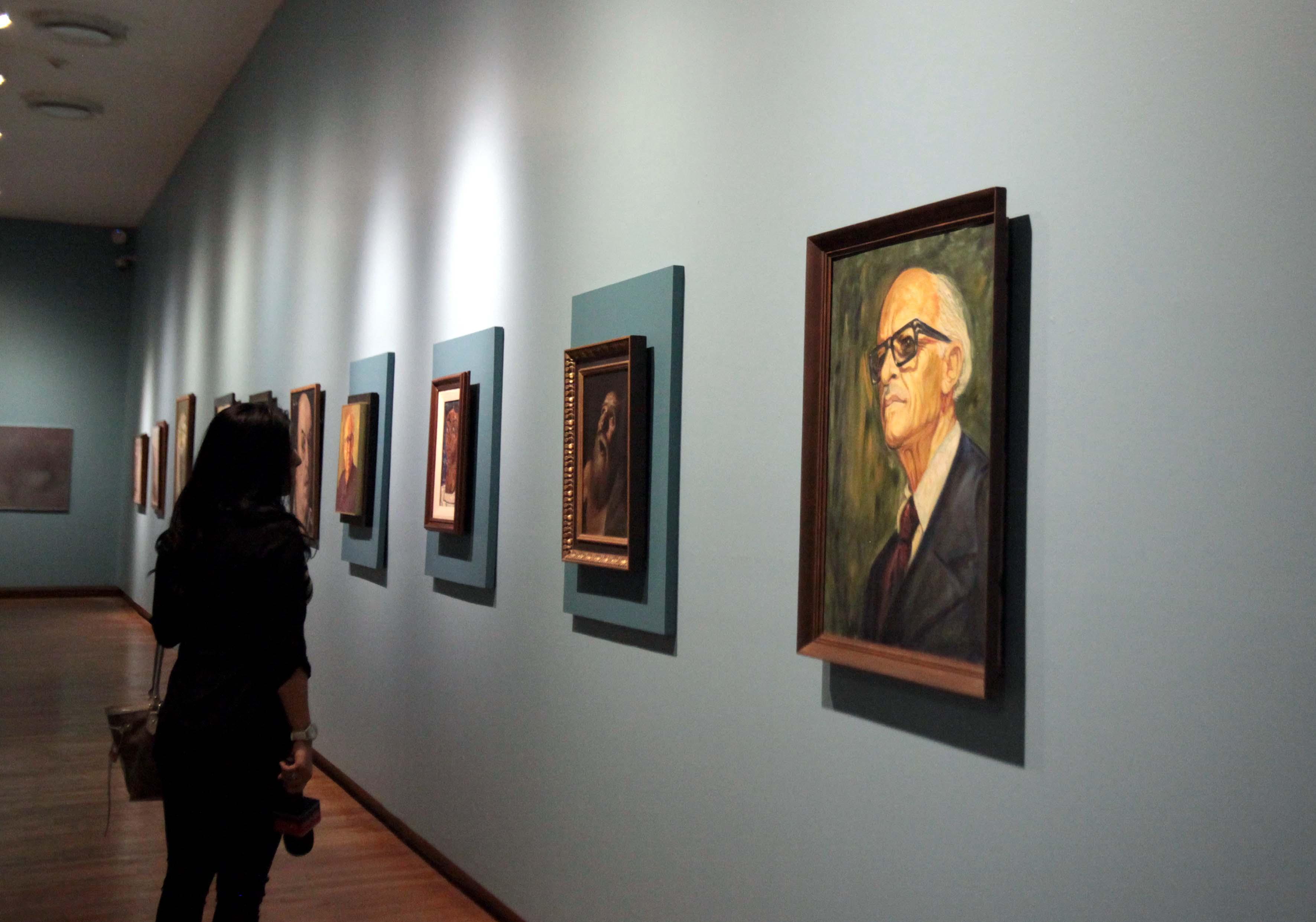 Asistente a la conferencia de prensa, observando en uno de los pasillos del MUSA, las obras artísticas universitarias.