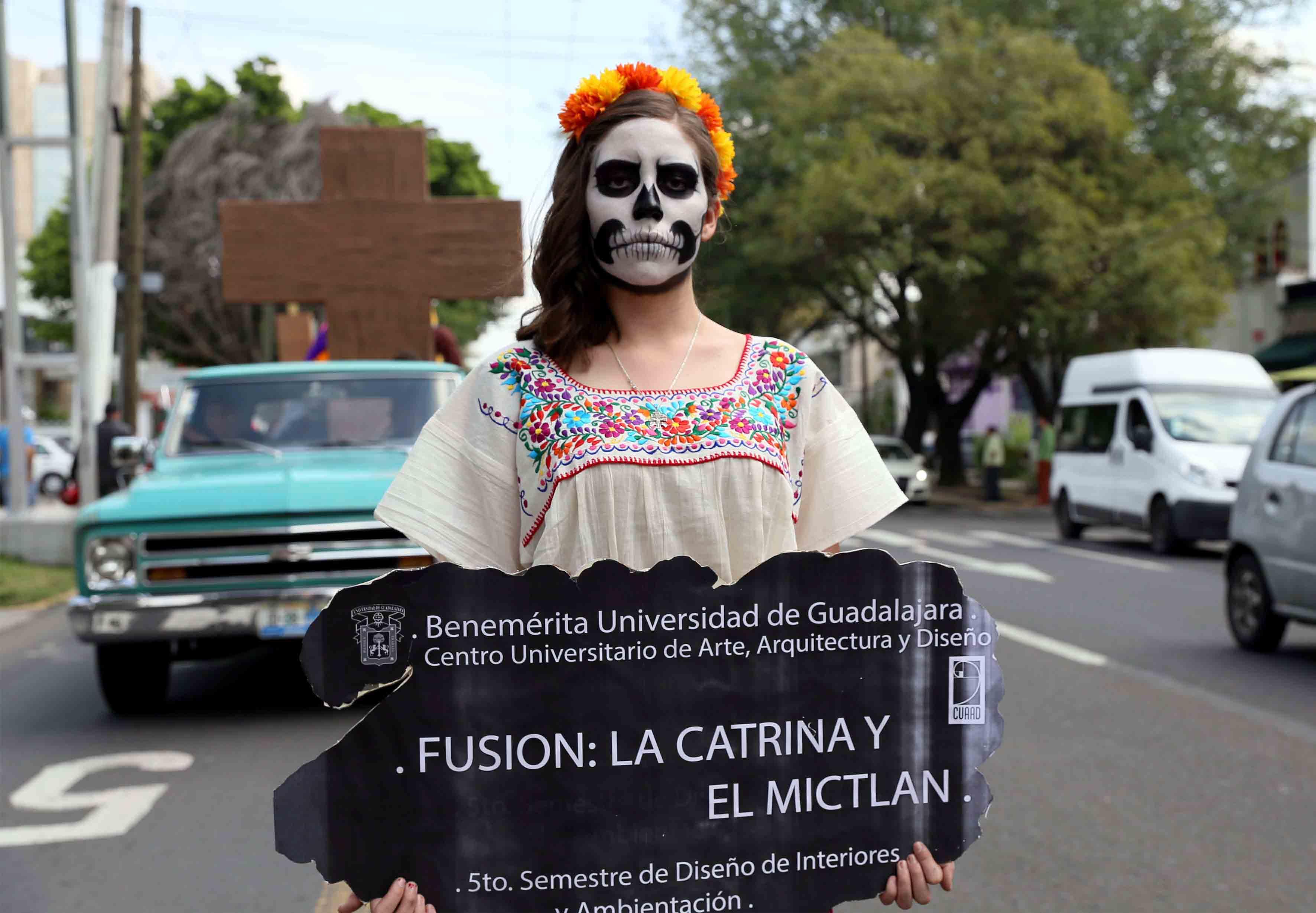 """Personificación de la muerte de una mujer cargando un letrero con la leyenda """"Fusión la catrina y el Mictlán"""" por parte de estudiante del CUAAD, durante desfile del Festival de la Muerte."""