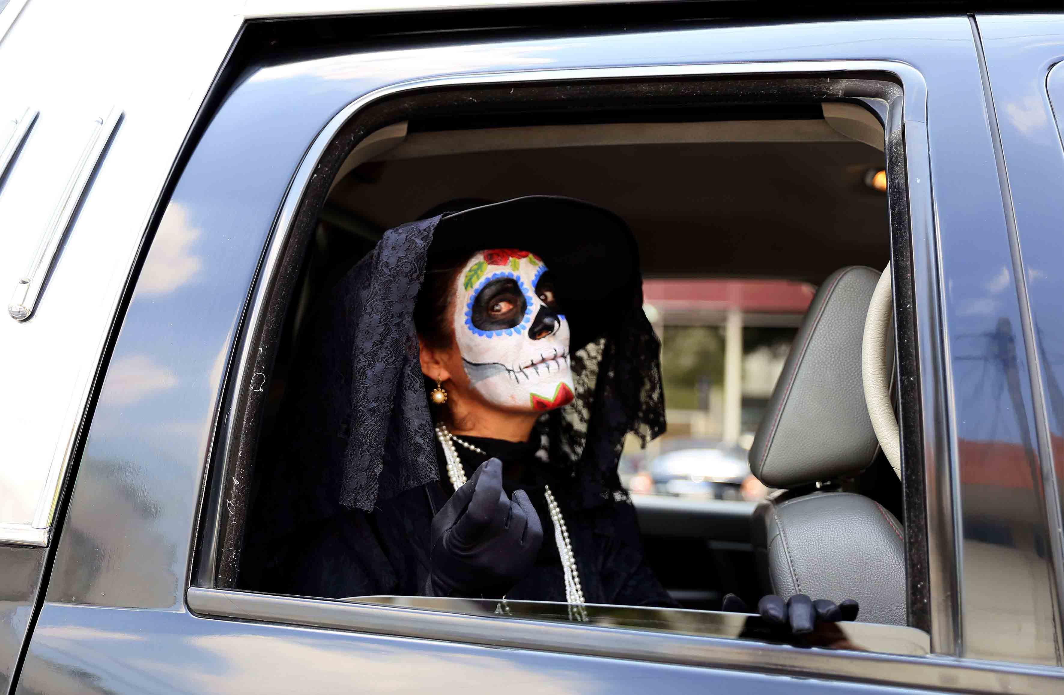 Foto lateral de catrina subida al interior de un carro, y haciendo la seña de llamado hacia ella con la mano.