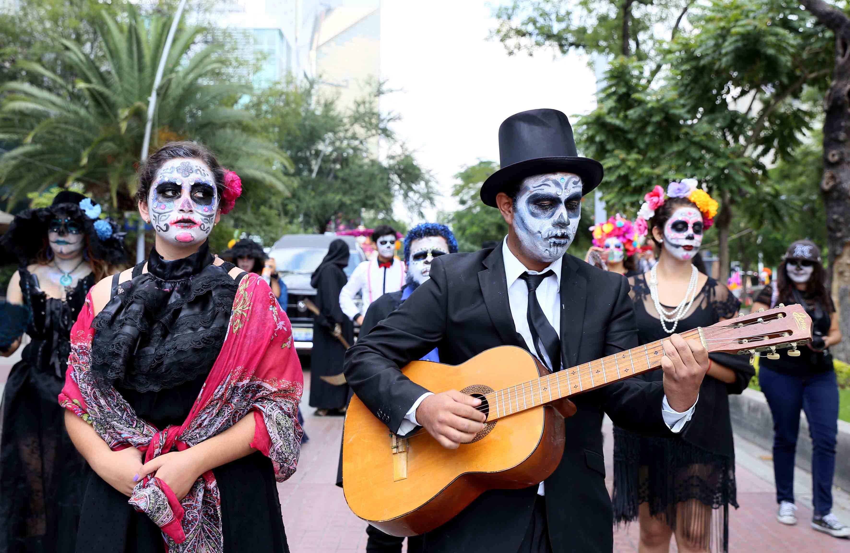 Personaje de catrin tocando la guitarra y rodeado de catrinas, durante desfile del Festival de la Muerte.