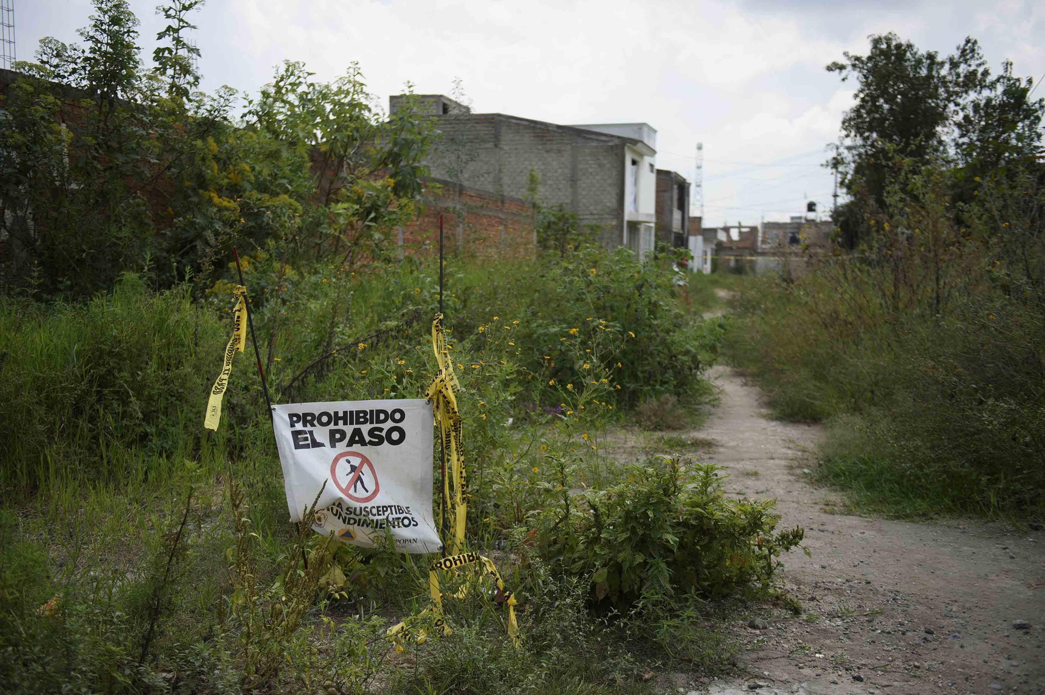 Baldio de matorrales con un letrero de prohibido el paso por hundimientos, cercano a zona habitada de nextipac.