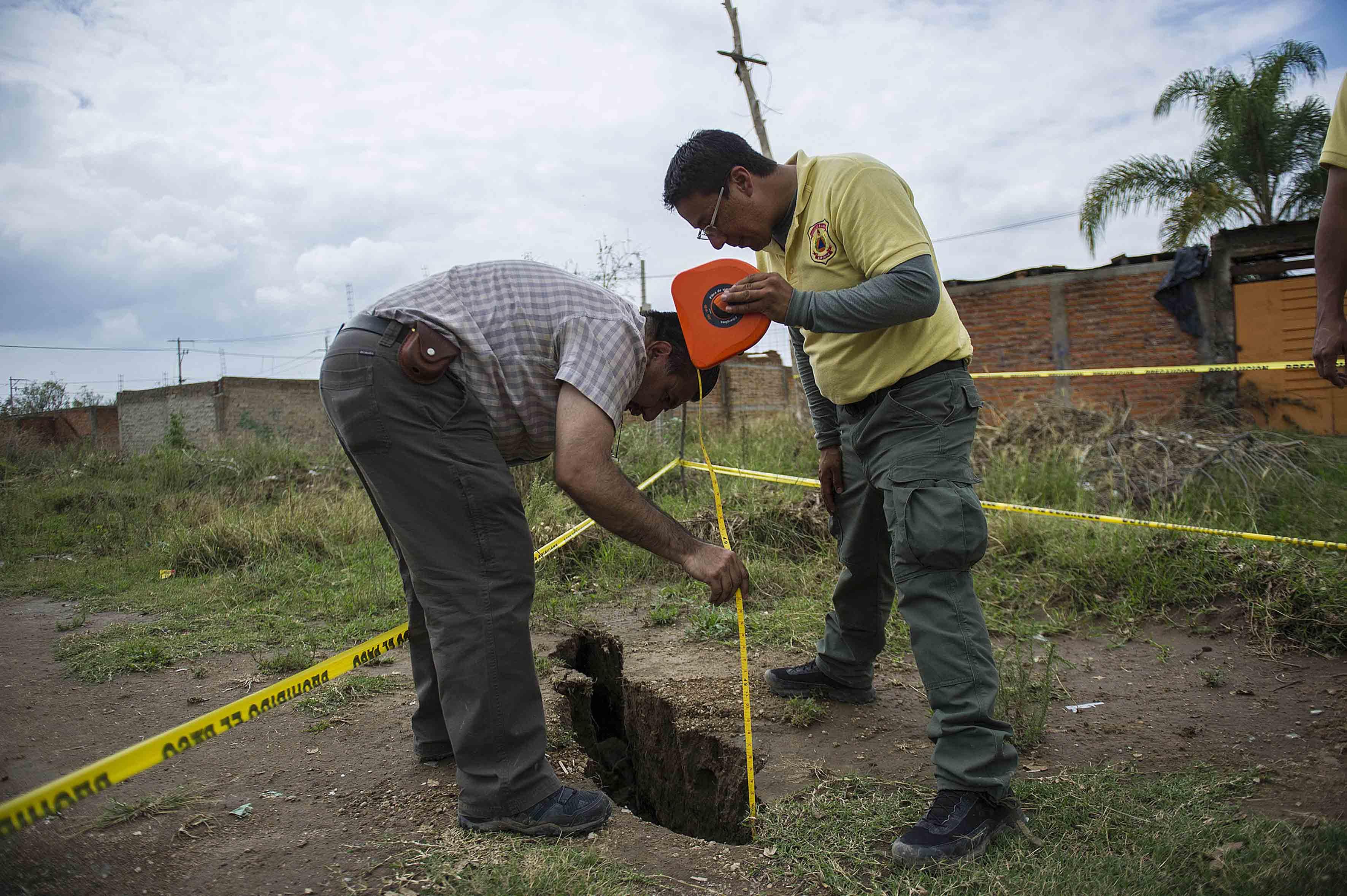Especialistas midiendo la profundidad de grieta en una de las zonas acordonadas en nextipac.