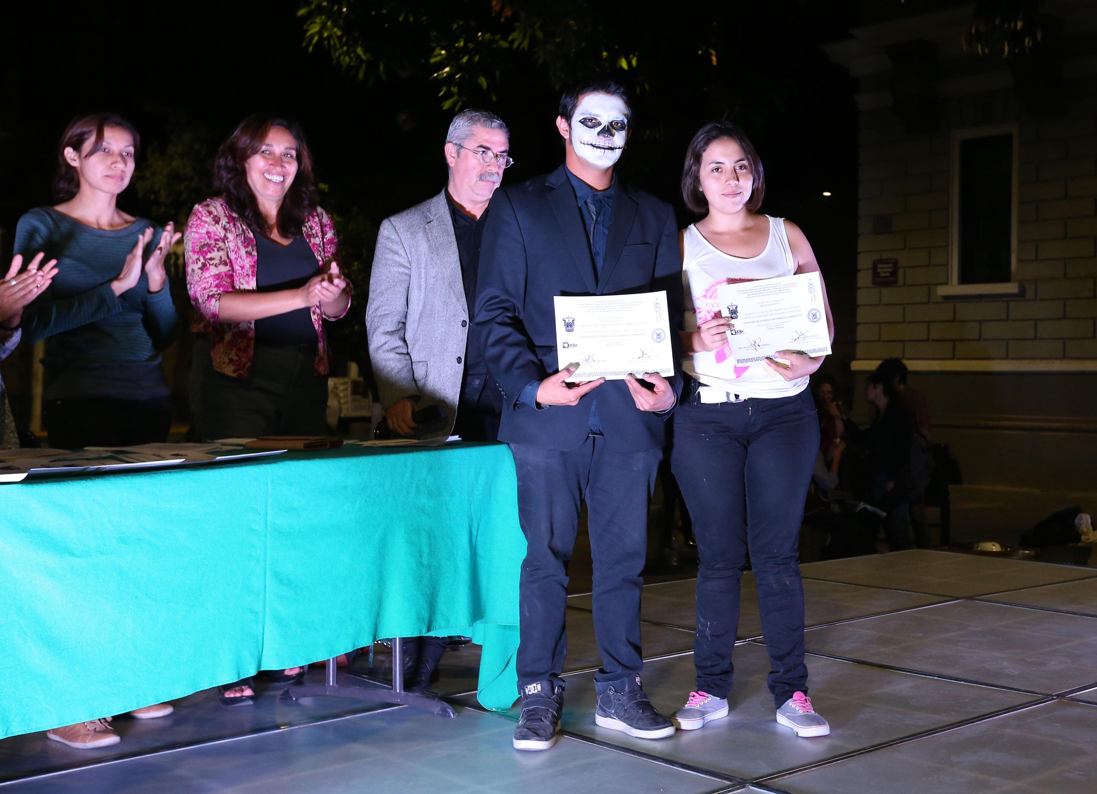 Estudiantes del CUCBA, paticipantes del concurso de tumbas con temática ambiental, portando su reconicimiento.