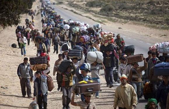 Grupo de migrantes caminando por una carretera