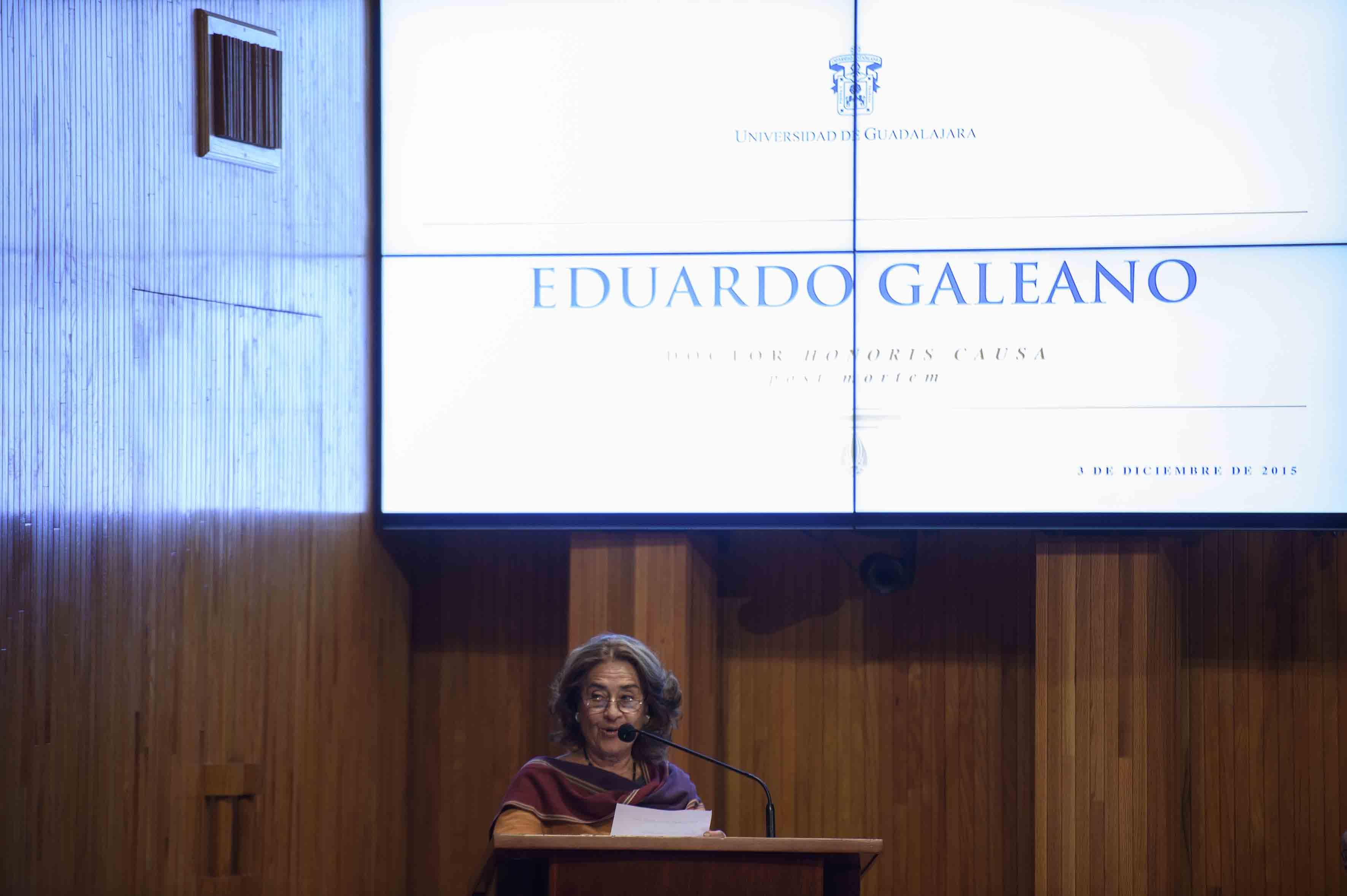 La señora Helena al frente del micrófono en el podio