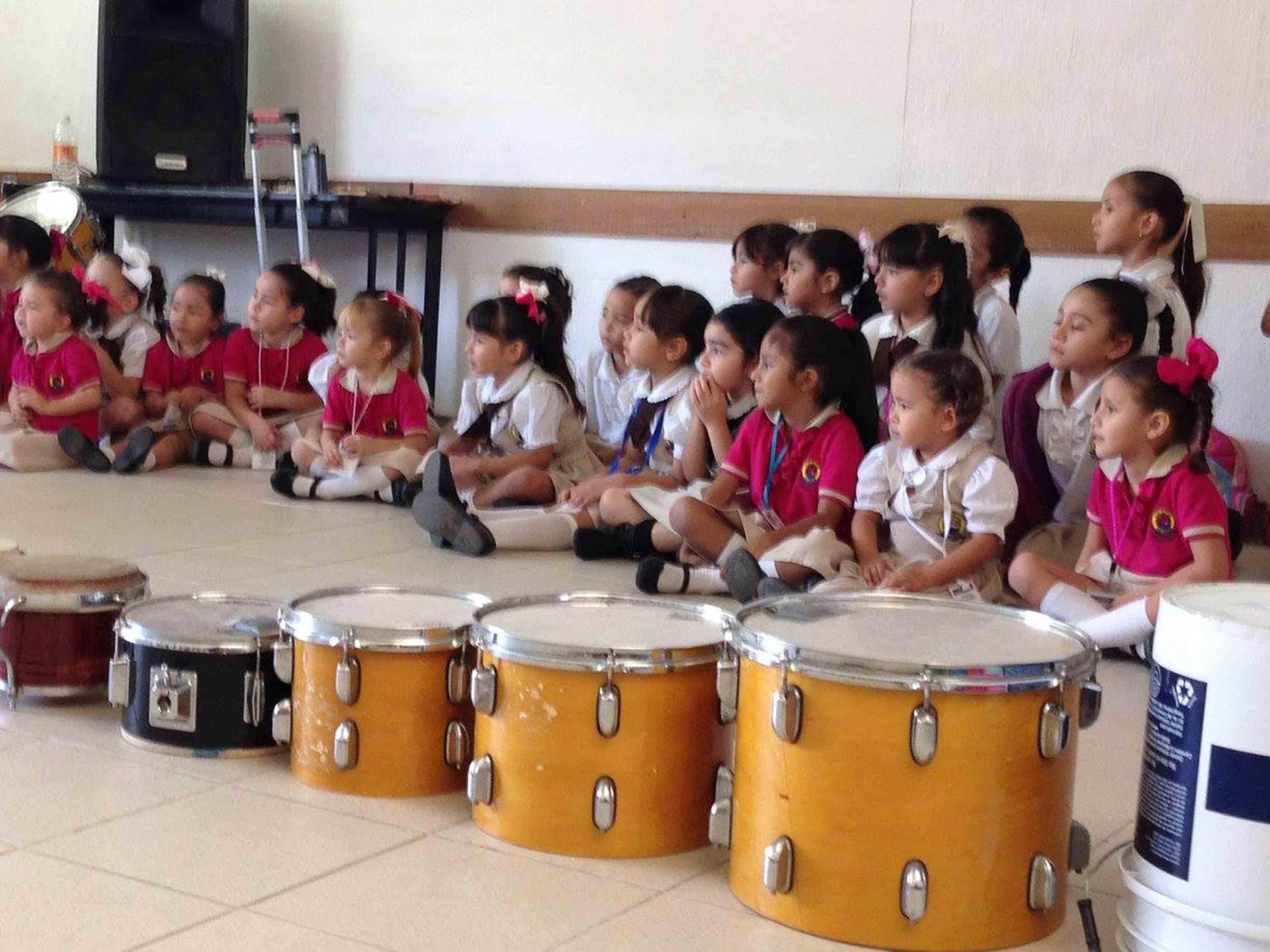 Niñas sentadas alrededor del piso y enfrente de ellas tambores colocados en forma horizontal por tamaño de menor a mayor.