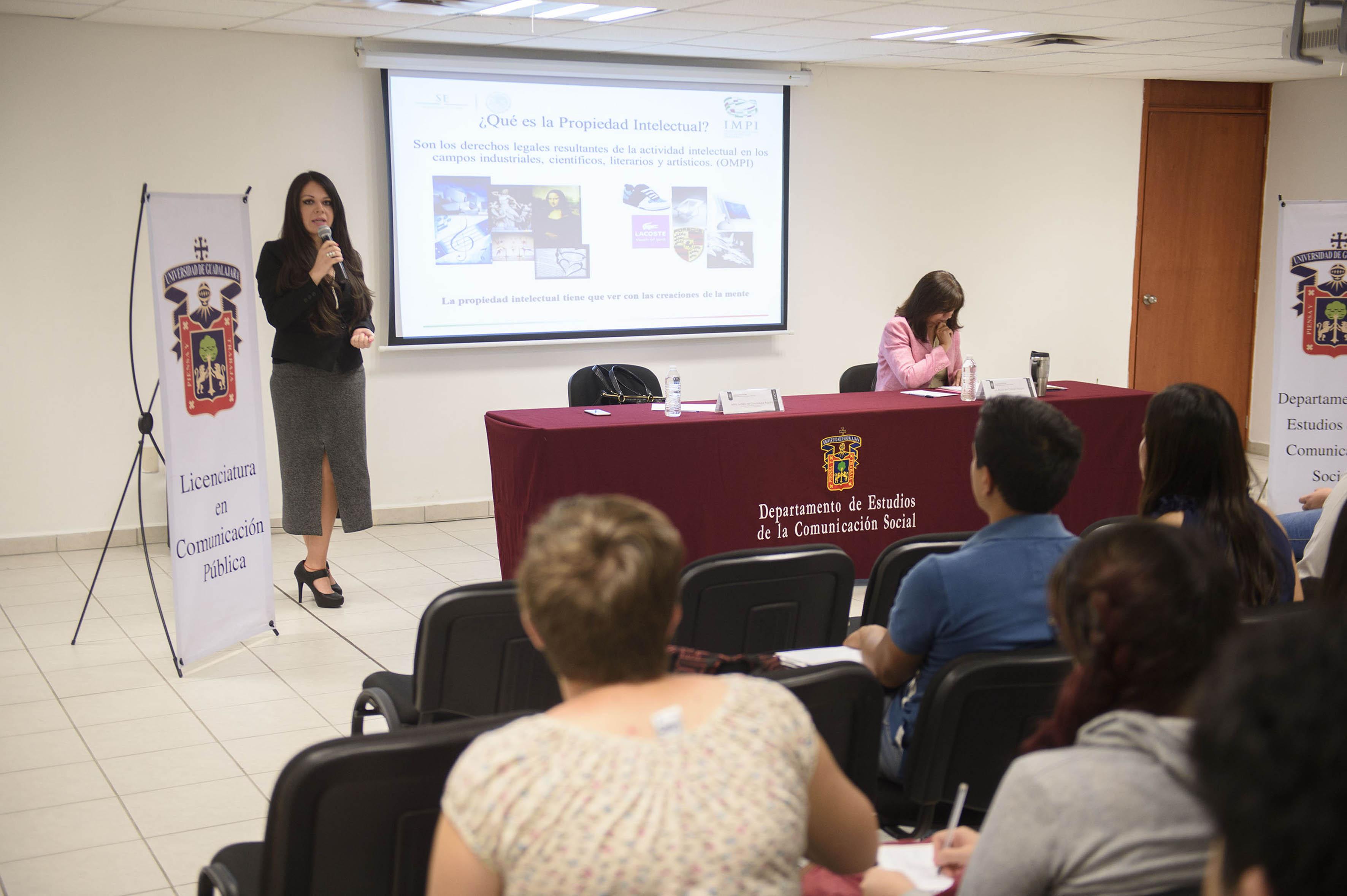 Mtra Lucero de Guadalupe Aguirre hablando frente al micrófono  en conferencia