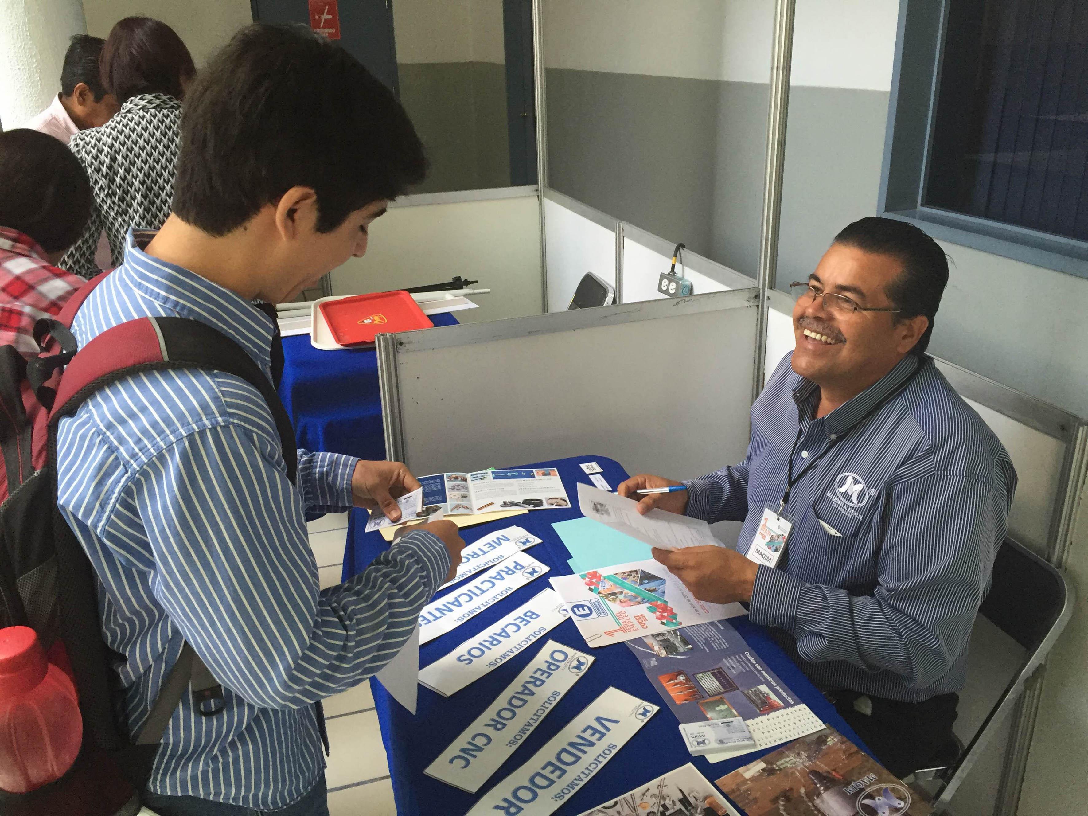 Reclutador entregando información y tarjeta de presentación a estudiante del CUCEI.