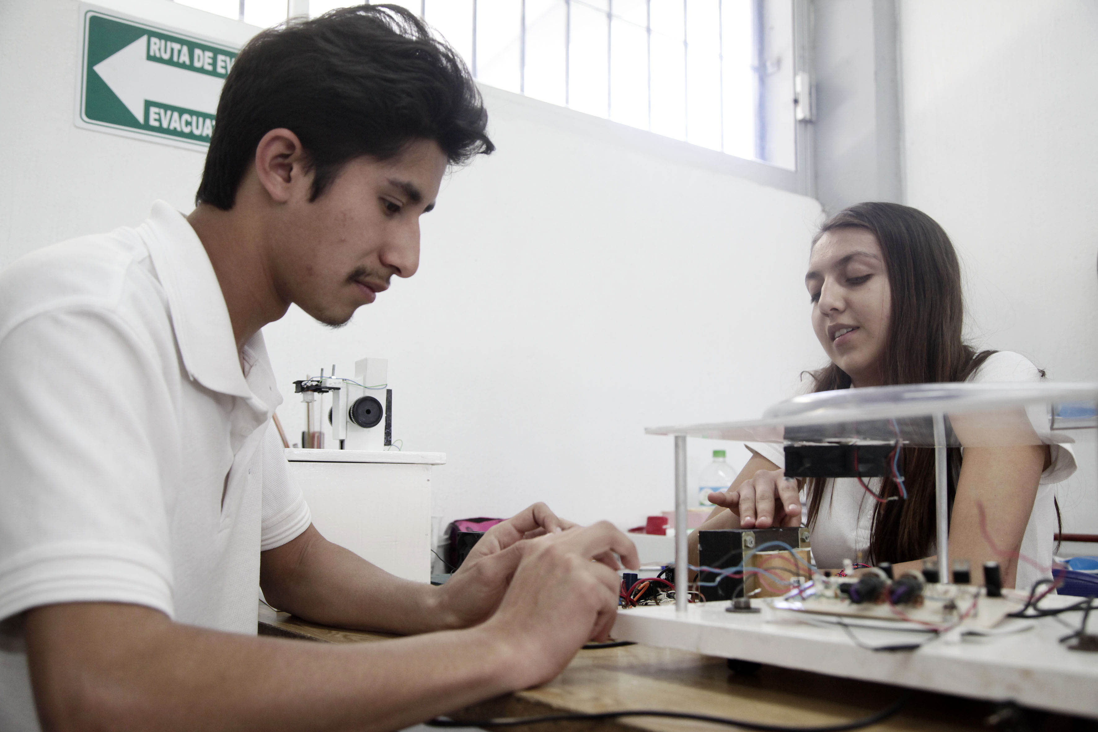 Martha Macías y Luis García alumnos de la Preparatoria Regional de Jocotepec, trabajando en uno de los prototipos elaborados con componentes electrónicos y material reutilizable para la feria internacional de ciencia celebrada en Turquía.