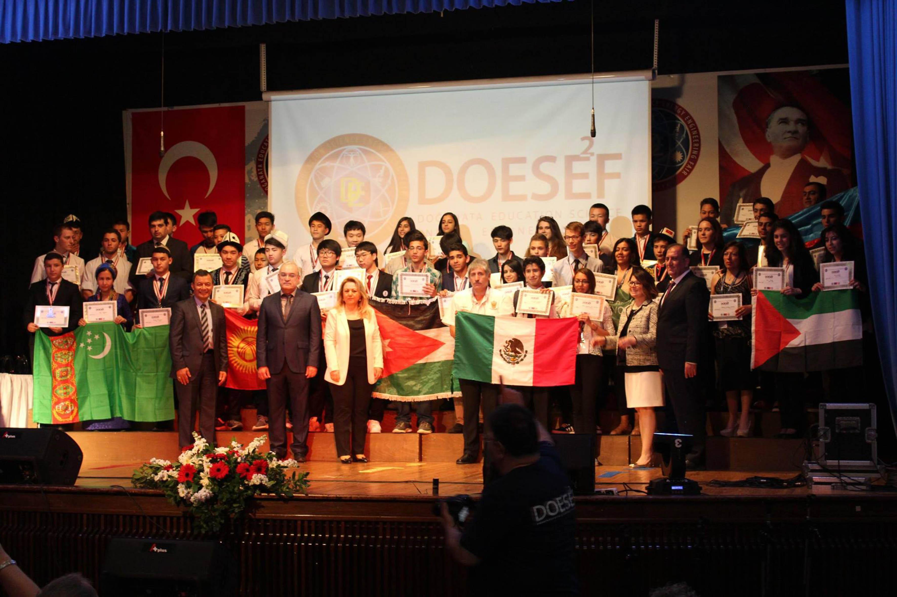 """Vista panorámica de los alumnos de todos los países participantes en la Feria Internacional de Ciencia """"Doğanata education science energy engineering fair"""", realizada en Izmir University, en Esmirna, Turquía; mostrando la bandera de su país y reconocimientos recibidos durante el evento."""