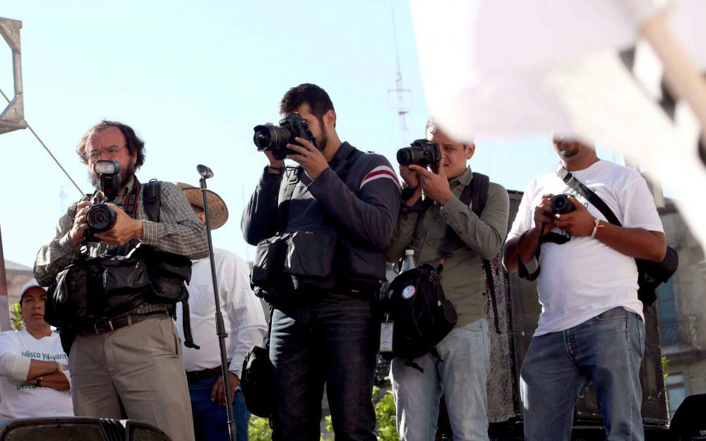 Personal de prensa con cámara profesional en función de actividades.