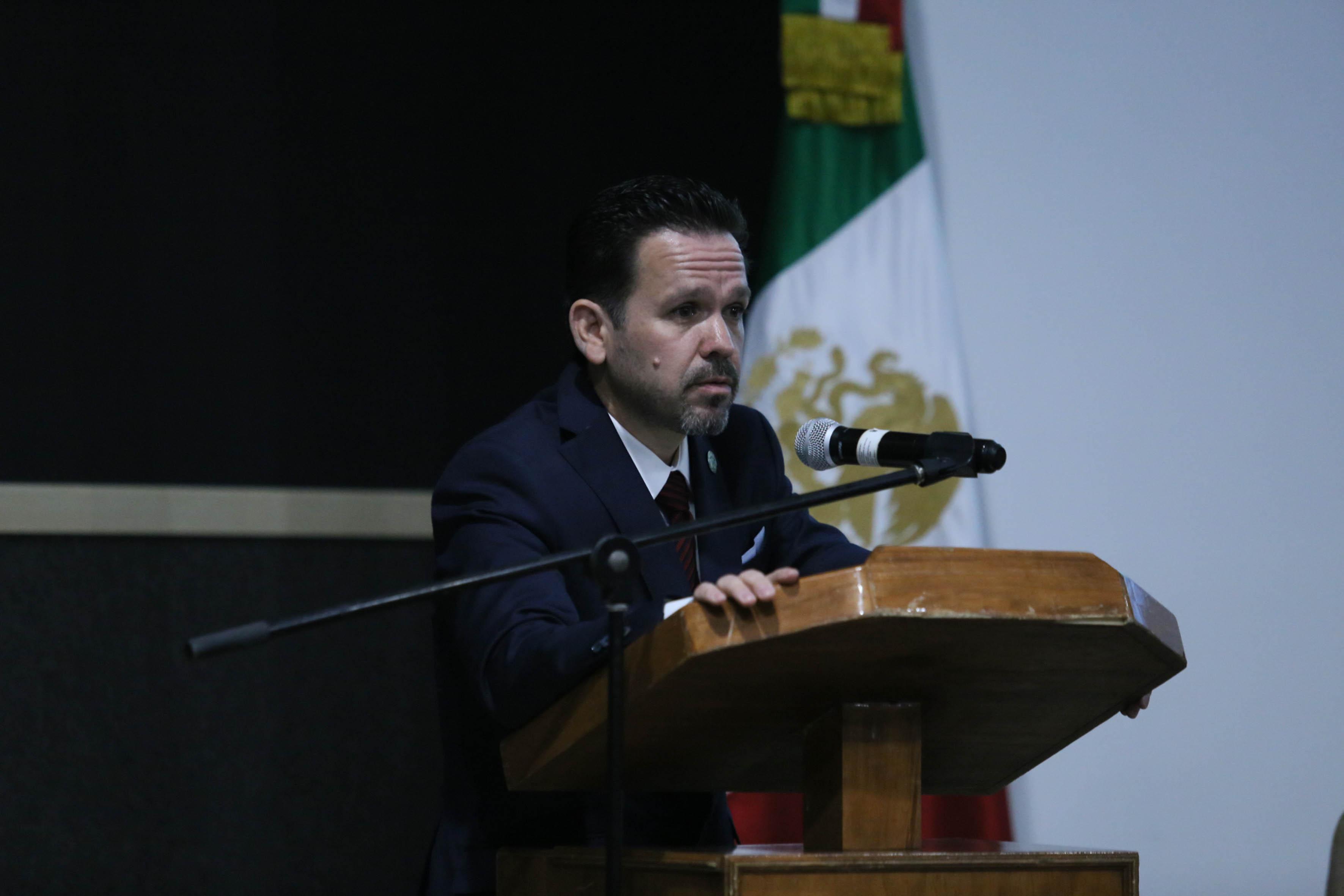 Doctor Aristarco Regalado Pinedo, nuevo Rector del CULagos, con micrófono en podium, haciendo uso de la palabra.