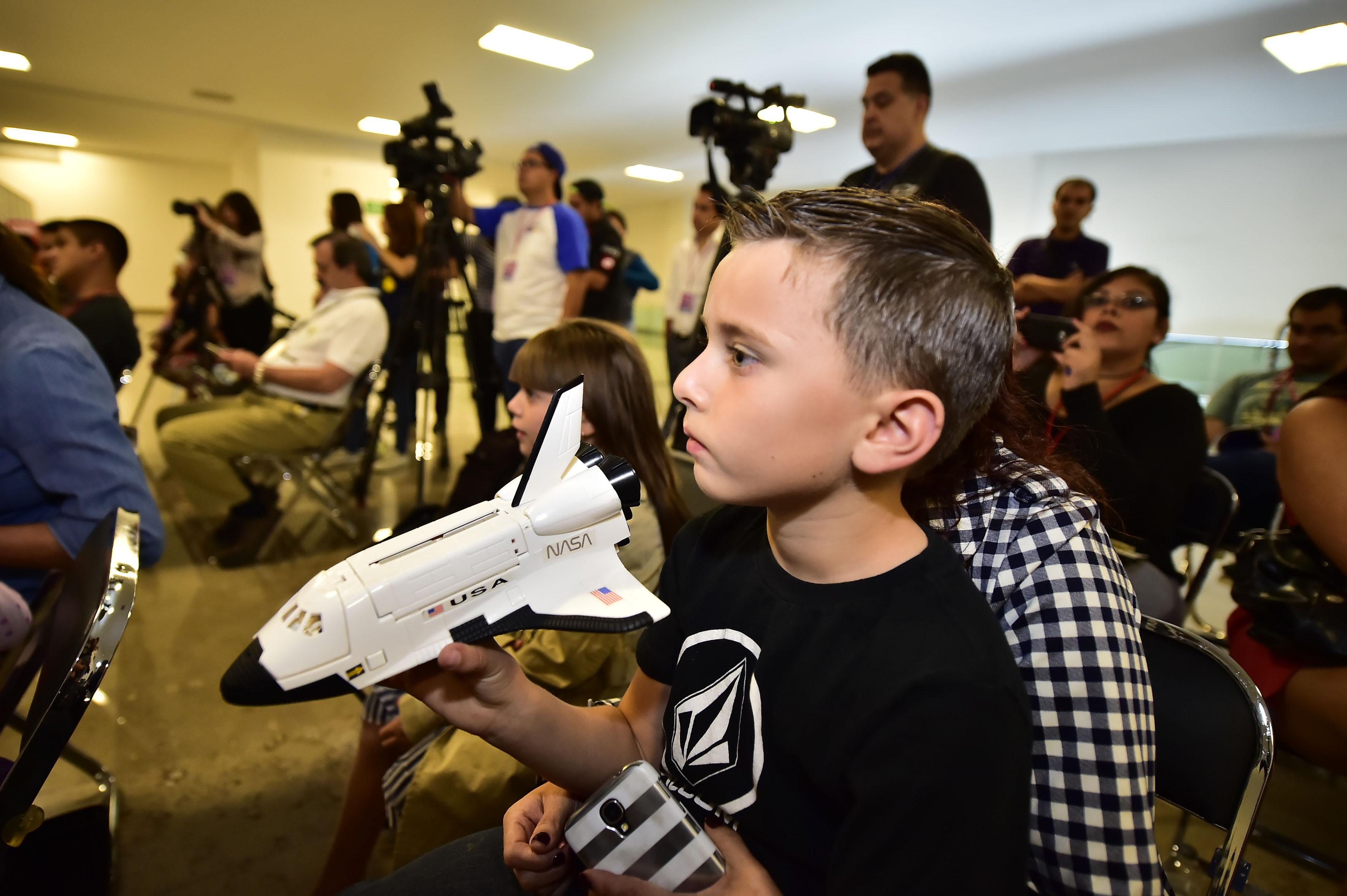 Niño con una nave espacial de juguete  participando en la conferencia del astronauta méxico-estadounidense José Hernández
