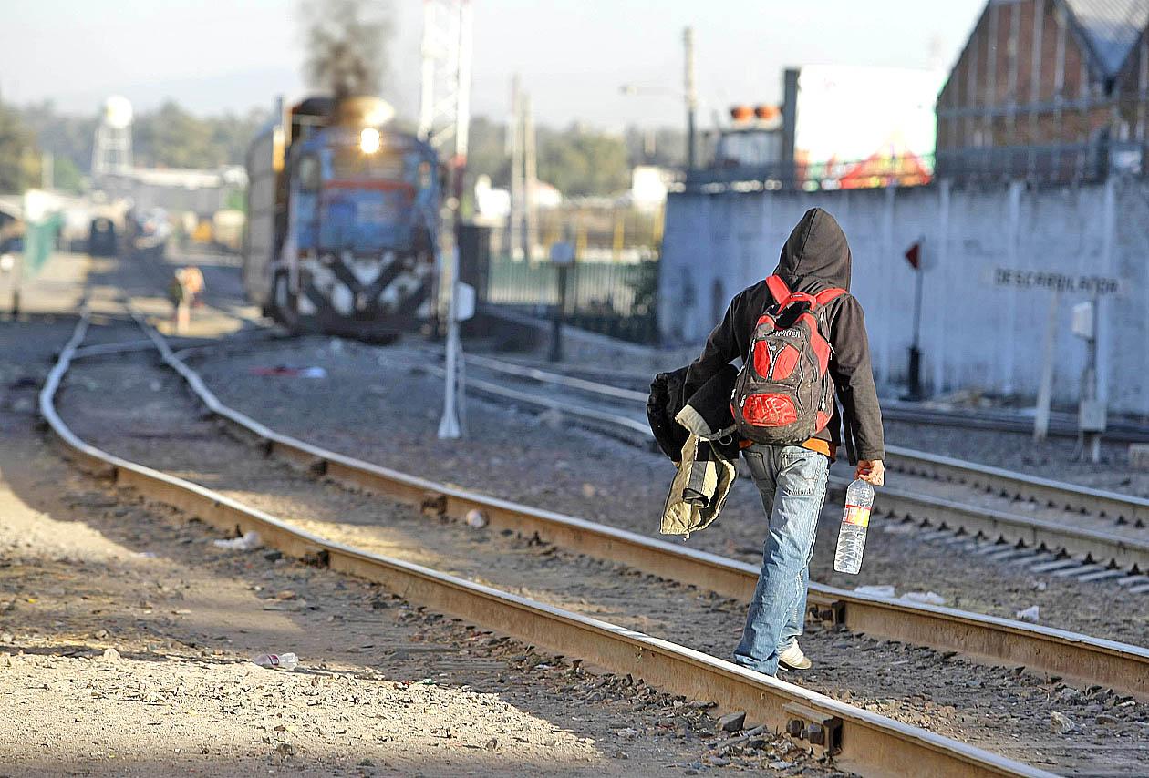 Migrante con mochila, botella de agua en mano y chamarra en brazos; cruzando los andenes de las vías del tren, mientras un ferrocarril se viene aproximando.