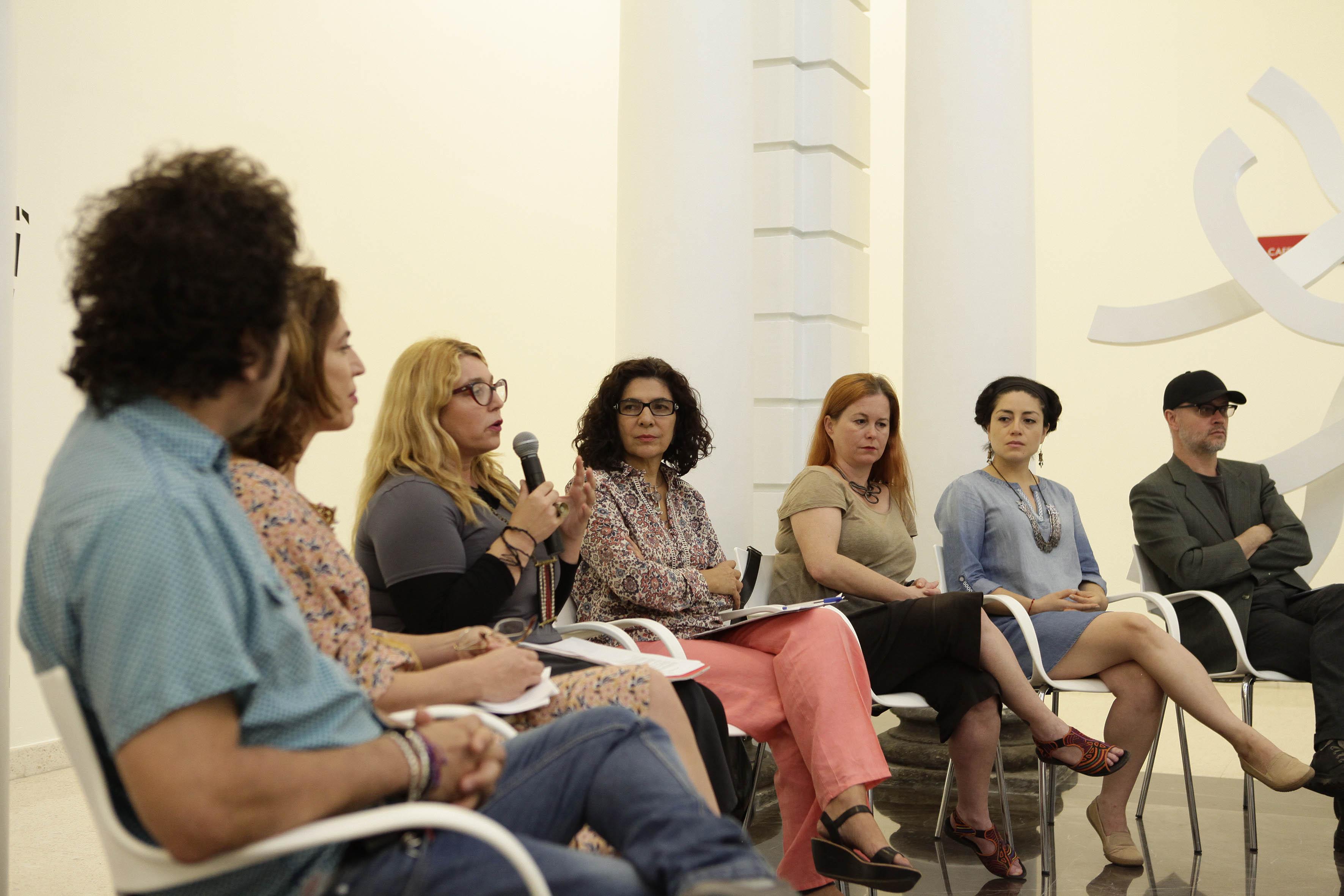 La doctora Marisa Caichiolo, encargada de la curaduría de la muestra en exposición, con micrófonoen mano haciendo uso de la palabra.