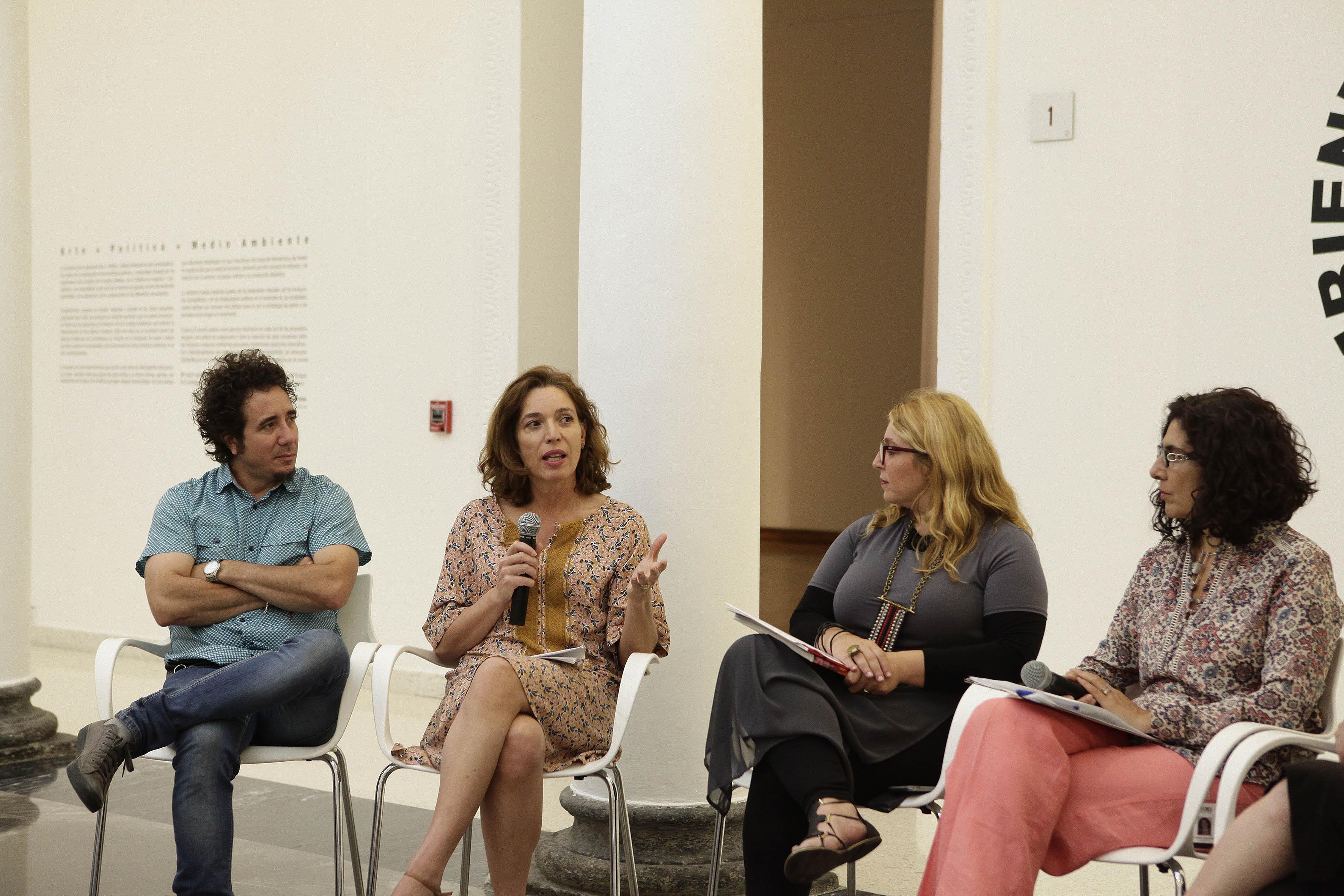 La argentina Andrea Juan, artista expositora en el MUSA, con micrófono en mano haciendo uso de la palabra.
