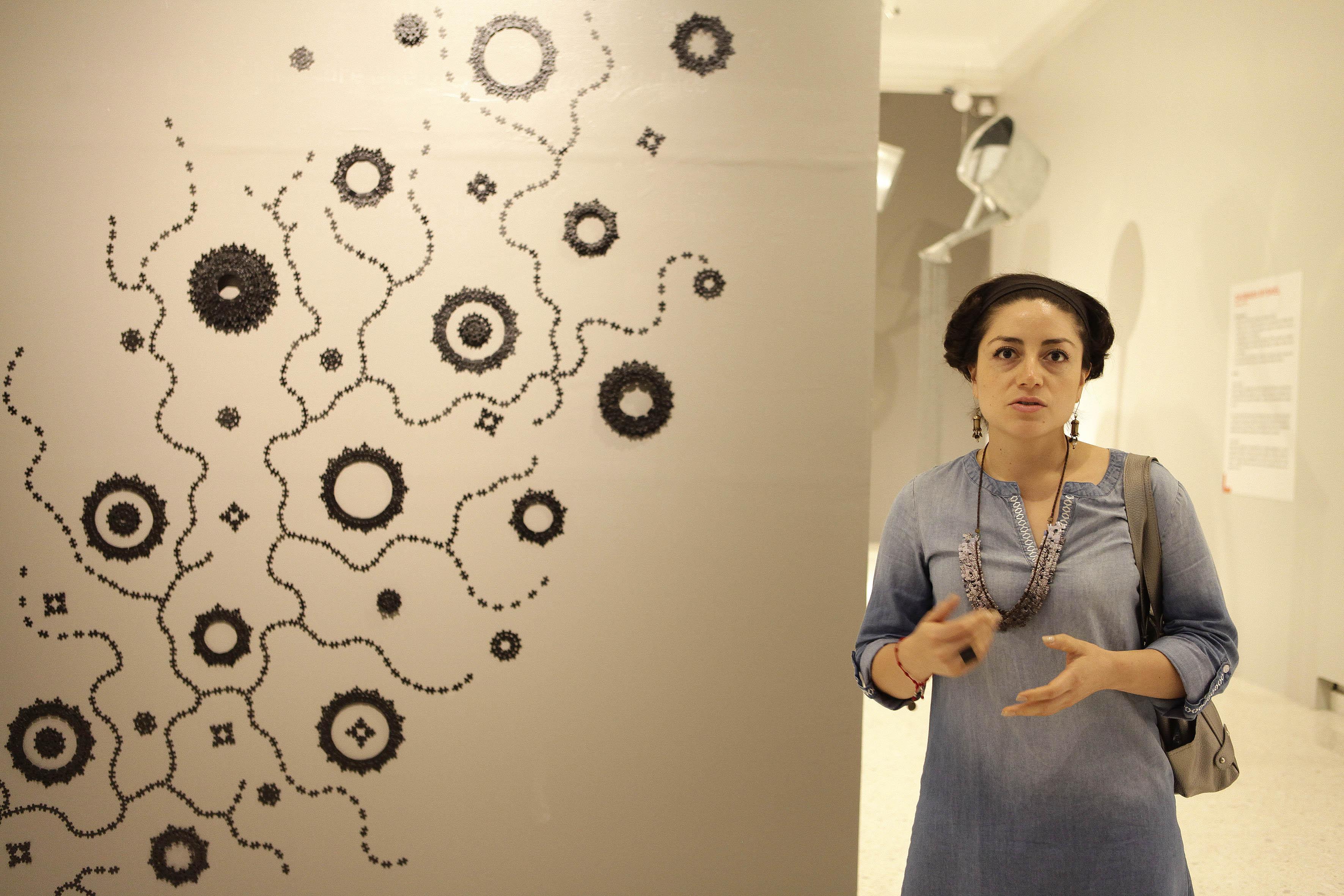 """La artista mexicana Karen Perry, a un lado de su obra en creación: """"Unidad de Construcción"""", haciendo una explicación."""