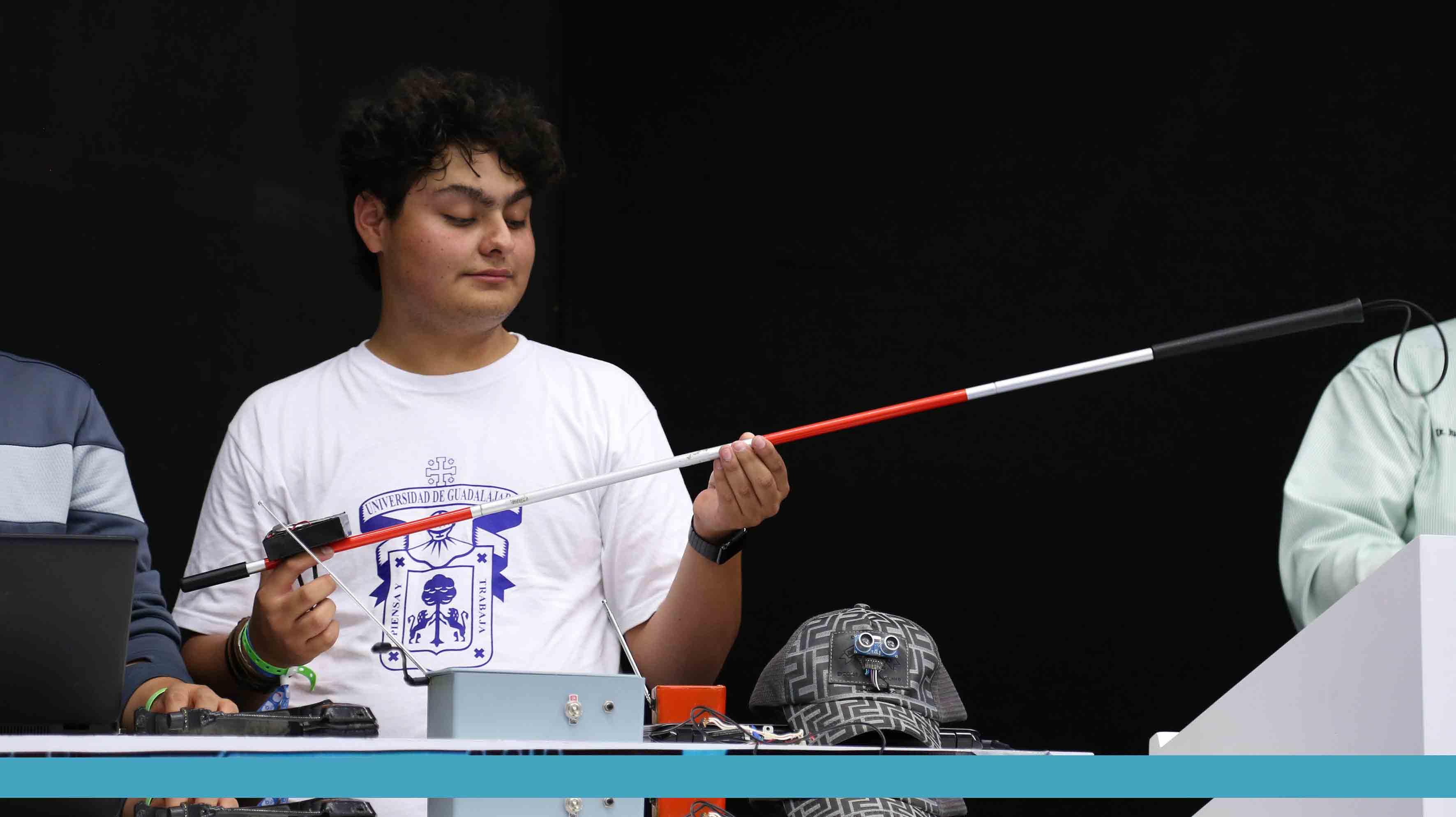 """Alumno, mostrando su invento """"bastón que alerta a las personas, sobre alguna irregularidad en el piso"""""""