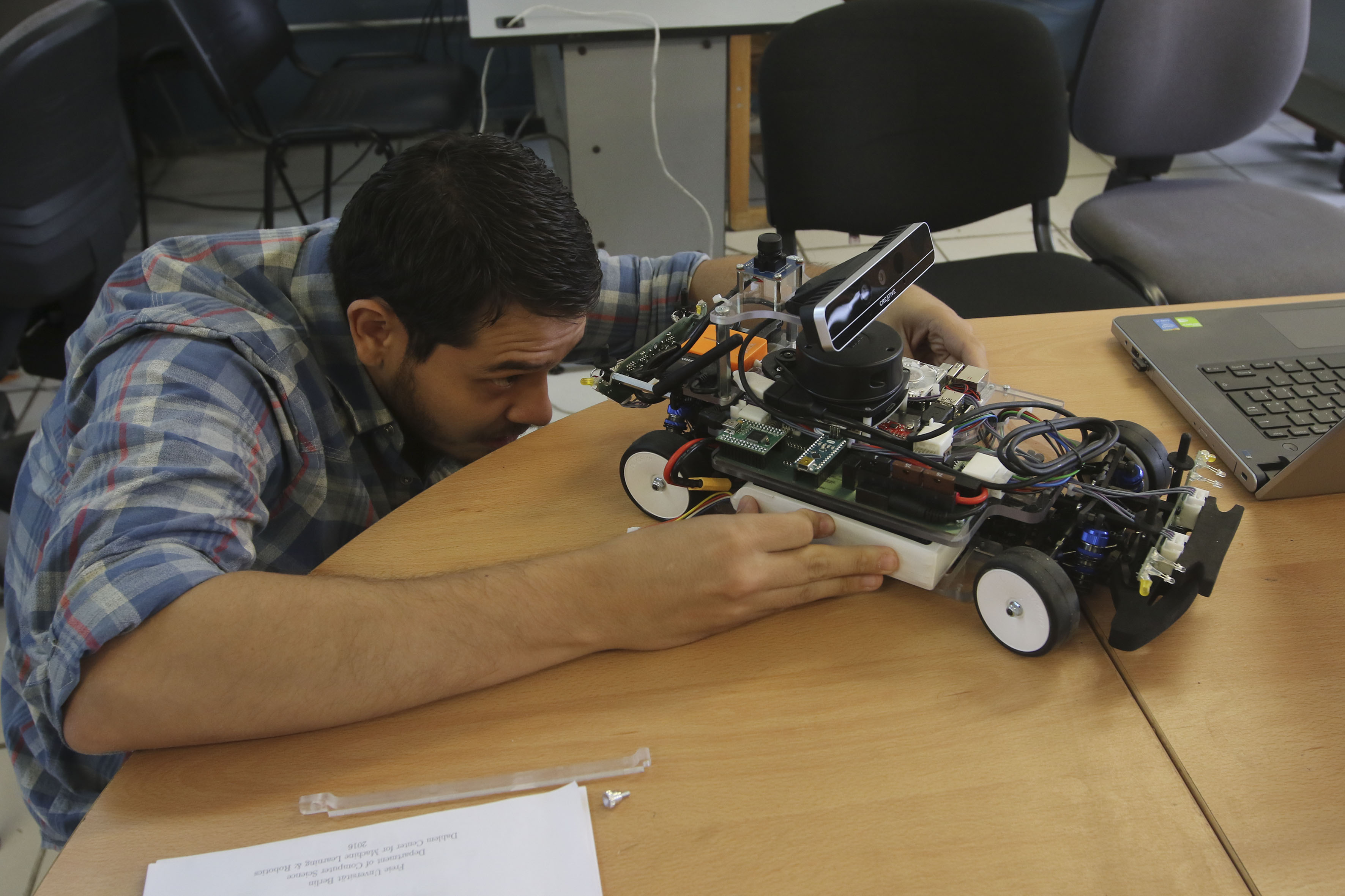 Integrante del equipo universitario del CUCEI, revisando el vehículo