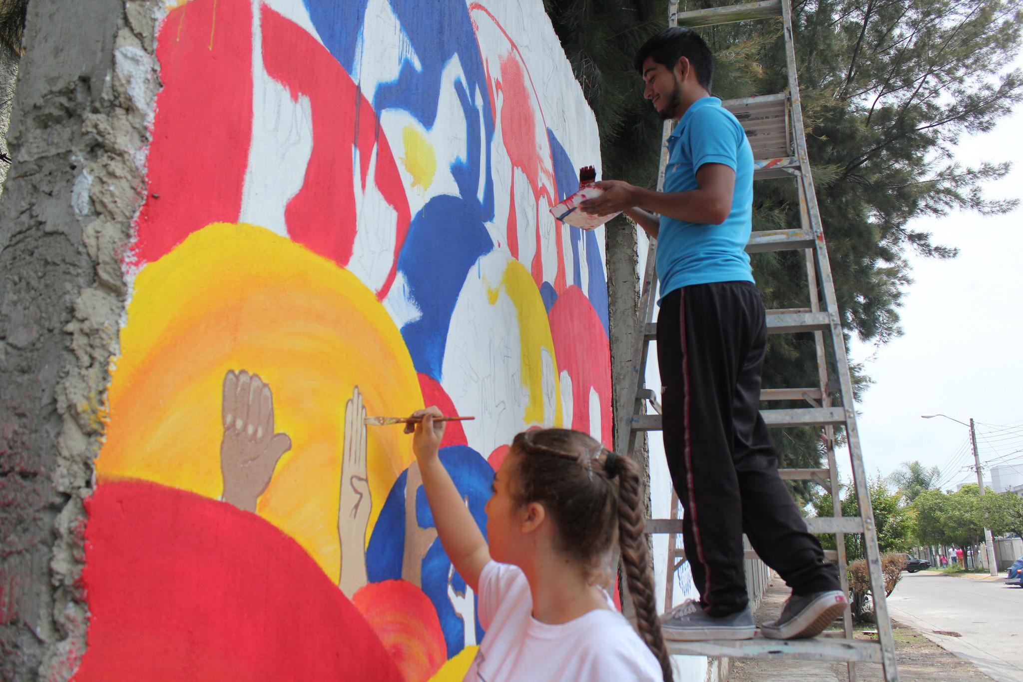 Alumnos de preparatoria No. 7 con discapacidad auditiva, pintando un mural con imgenes de lenguaje de señas