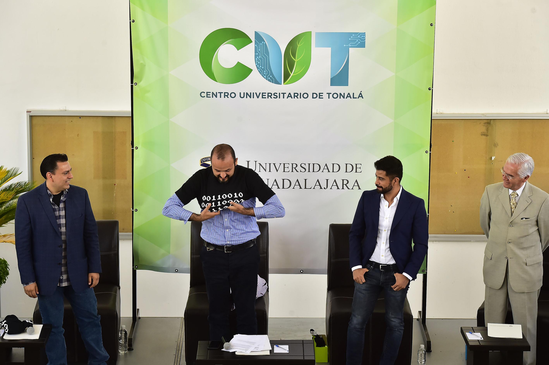 Rector del CUTonalá, doctor Ricardo Villanueva Lomelí, poniéndos una camiseta con representación del código binario para dar inicio a la primera jornada tecnológica.