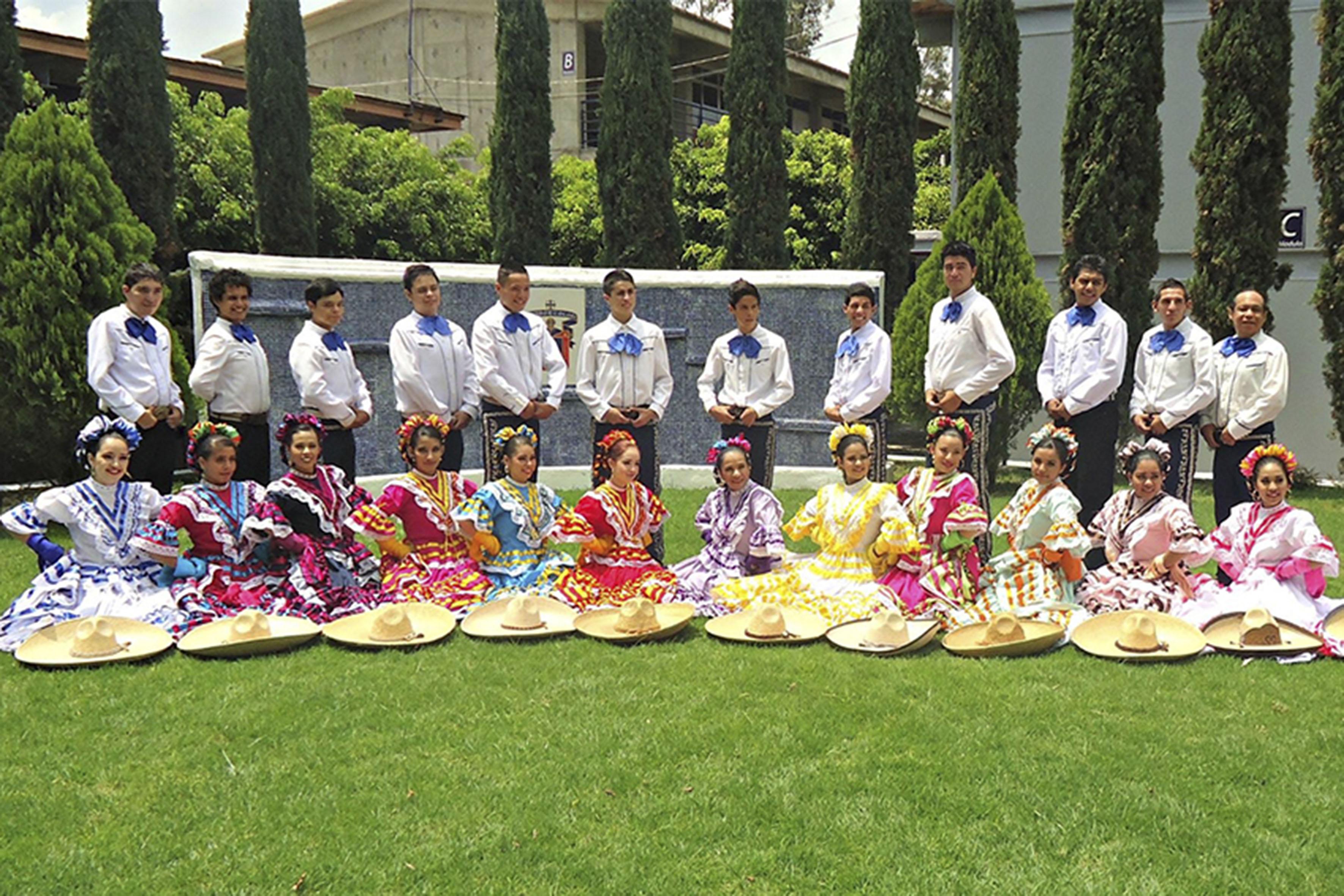 Estudiantes y representantes del grupo folclórico de la Preparatoria de El Salto de la Universidad de Guadalajara, con vestimenta típica, posando dentro de uno de los jardindes de sus instalaciones.