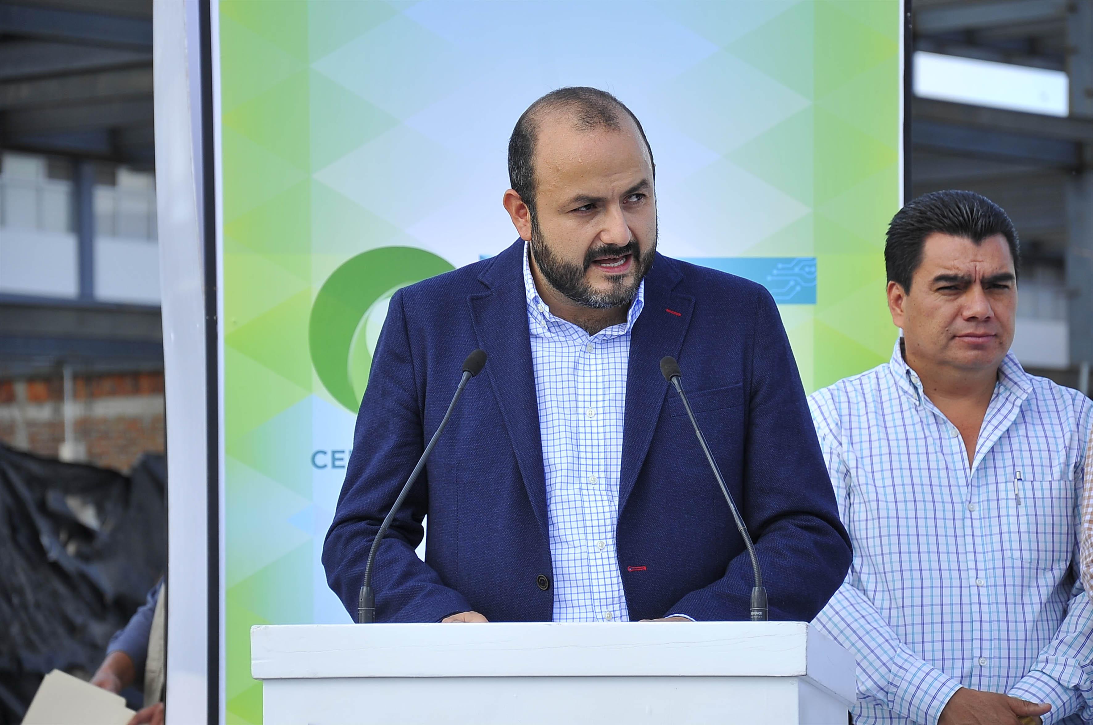Doctor Ricardo Villanueva Lomelí, Rector del centro, con micrófono en podium haciendo uso de la palabra.