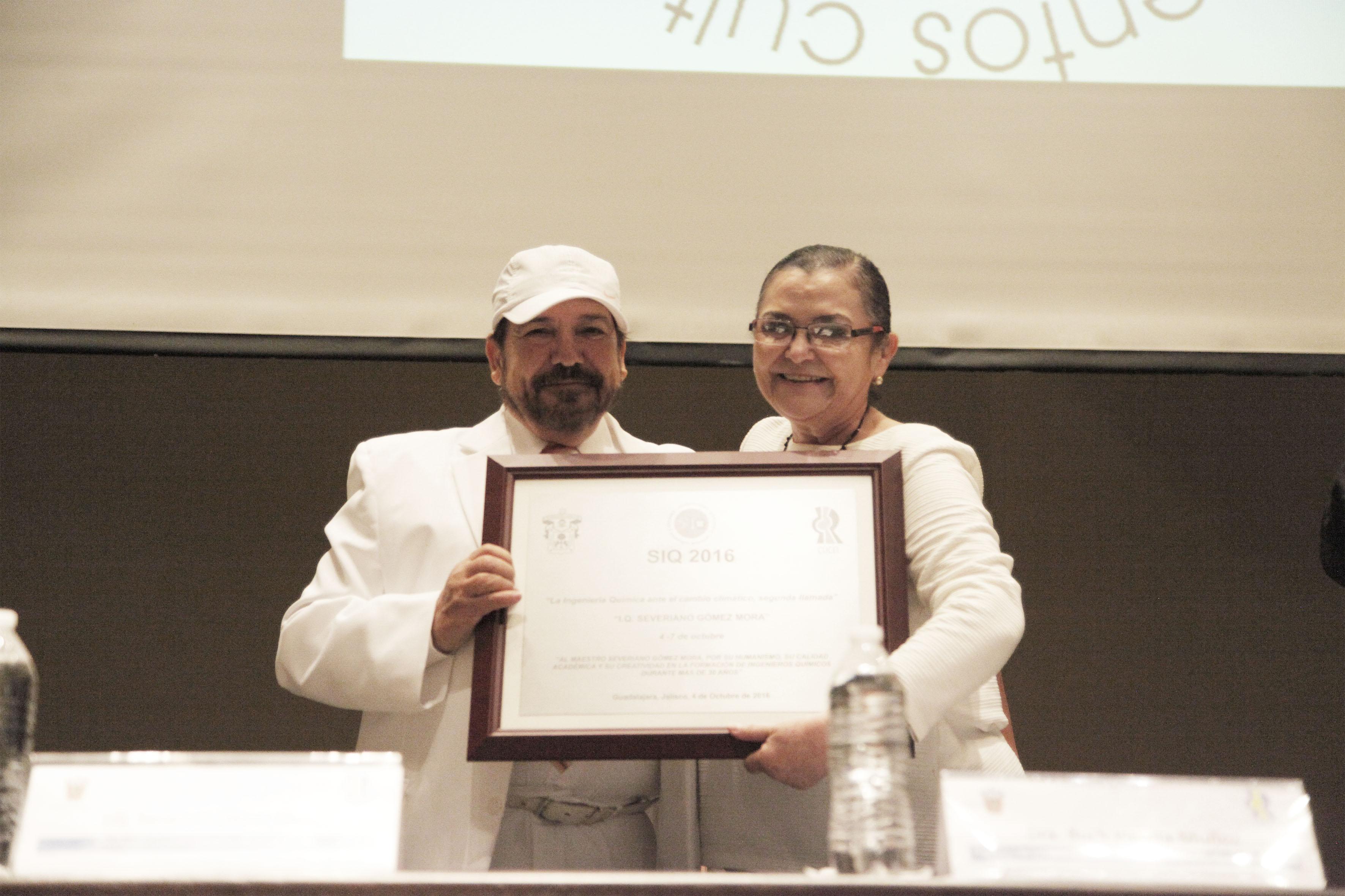 Ingeniero Severiano Gómez Mora, profesor de la carrera de Química y Doctora Ruth Padilla Muñoz, Rectora del CUCEI, mostrando la placa conmemorativa SIQ 2016 y de reconocimiento al profesor.