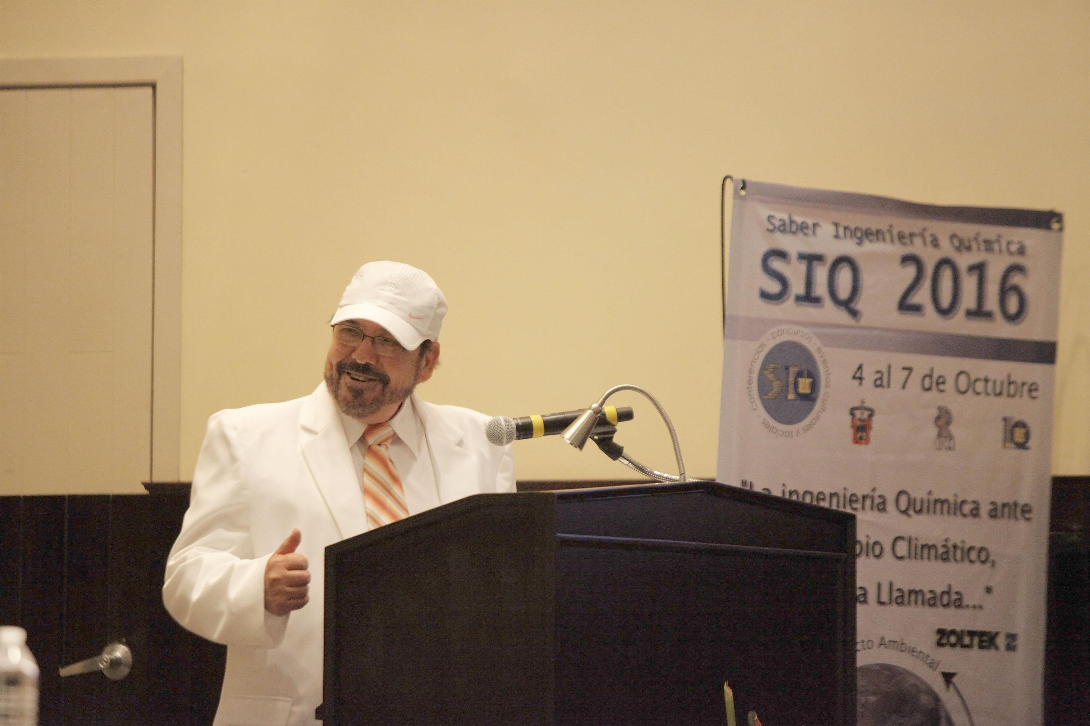 Vestido de traje en blanco y cachucha del mismo color, el Ingeniero Severiano Gómez Mora, profesor de la carrera de Química, con micrófono en podium haciendo uso de la palabra.