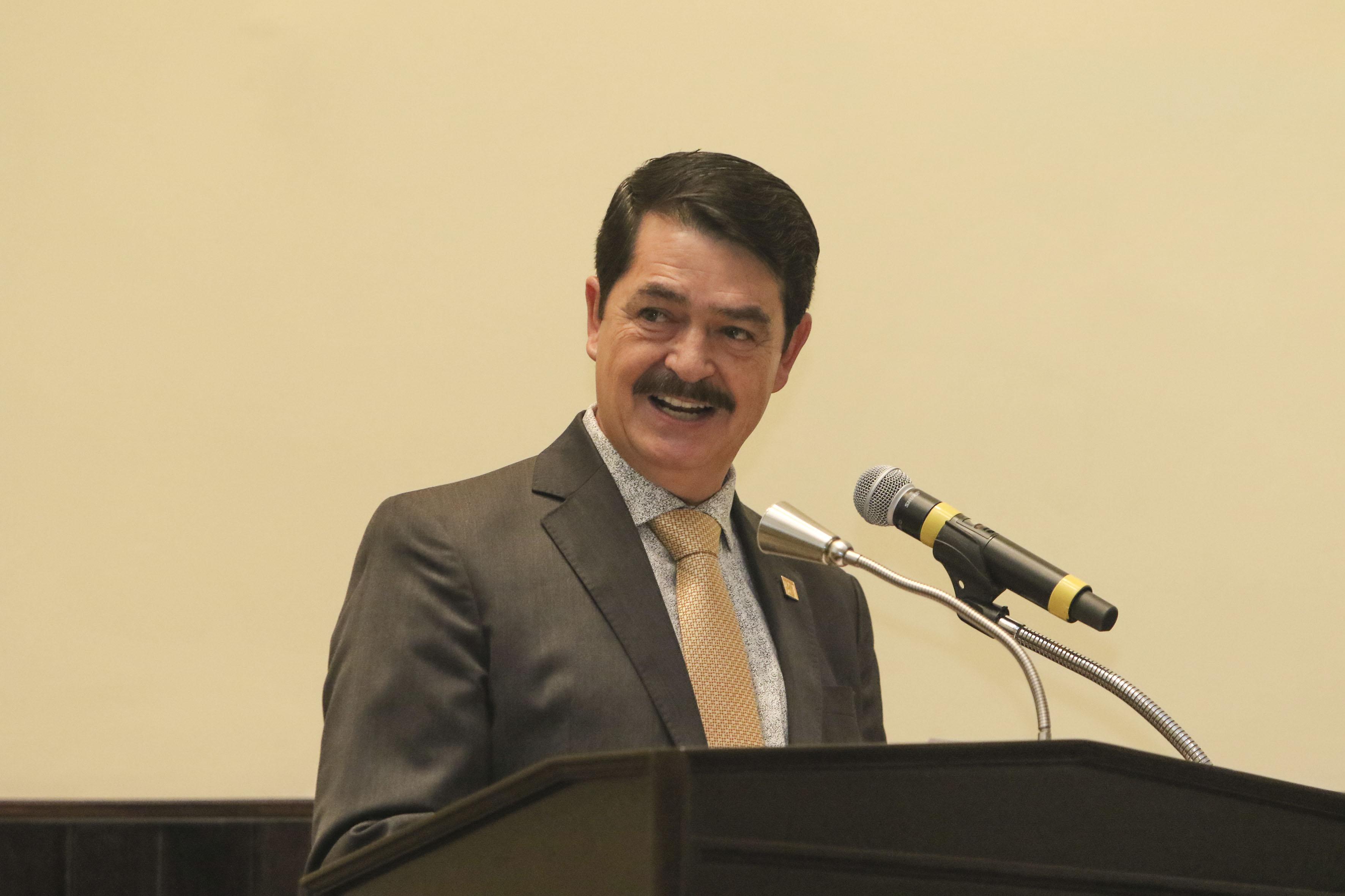 Doctor Carlos Pelayo Ortiz, secretario académico del CUCEI, en podium del auditorio haciendo uso de la palabra.