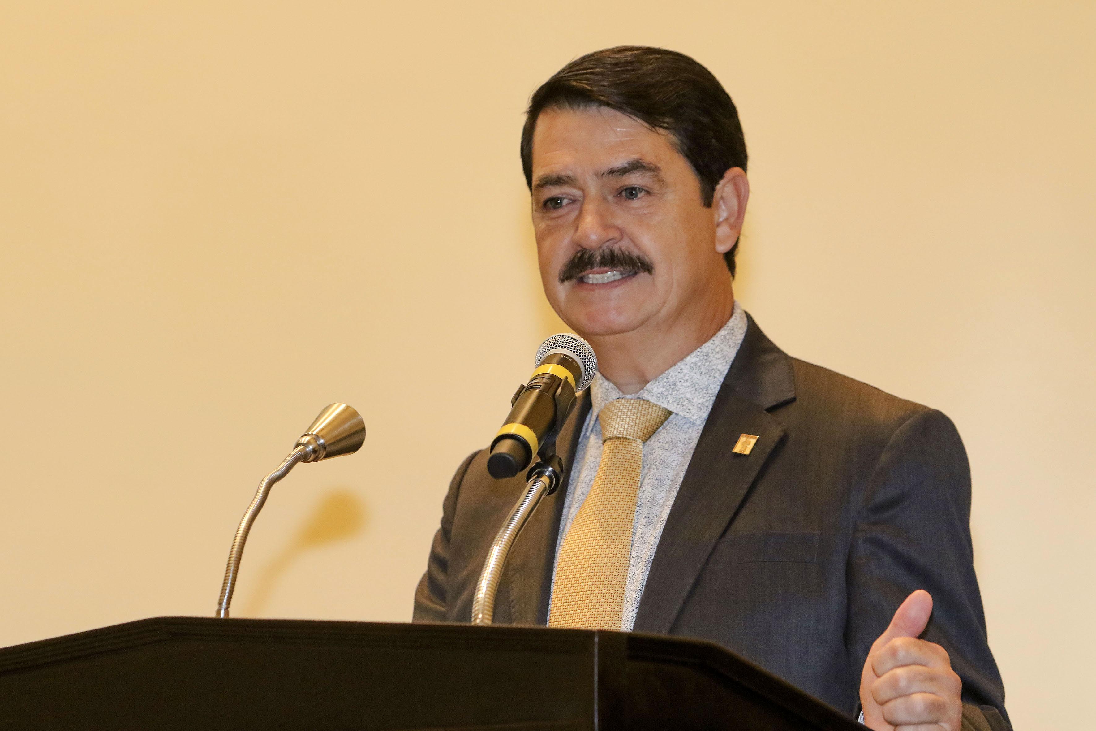 Doctor Carlos Pelayo Ortiz, secretario académico del CUCEI, con micrófono en podium del auditorio haciendo uso de la palabra.