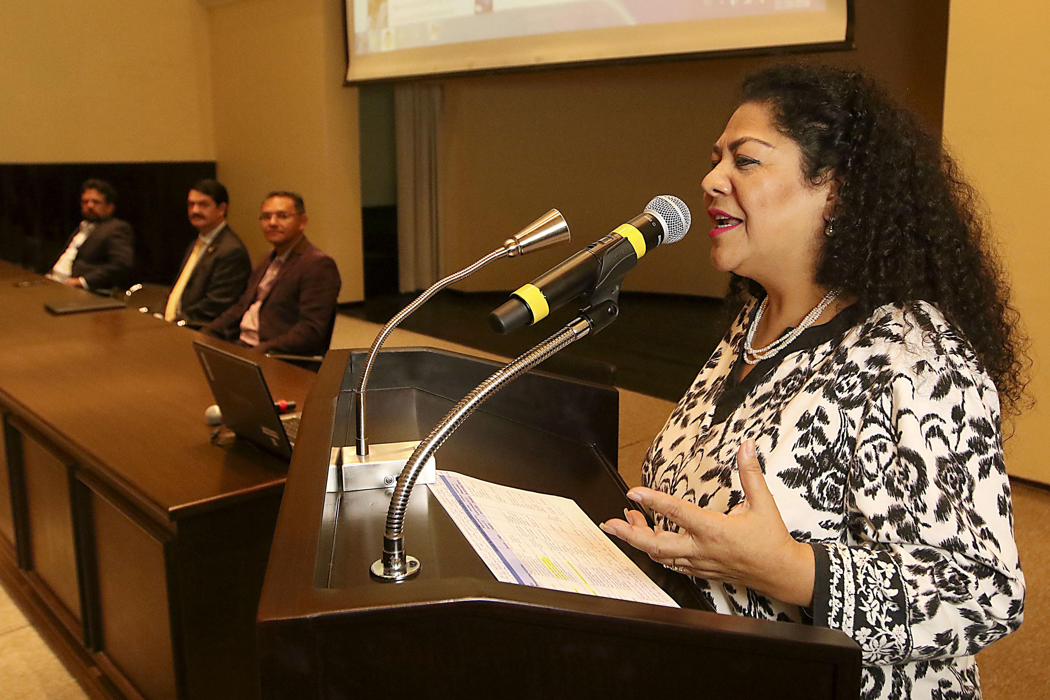Maestra Margarita Franco Gordo, jefa del Área de Integración y Difusión Educativa de la CIEP, con micrófono en podium del auditorio del CUCEI, haciendo uso de la palabra.