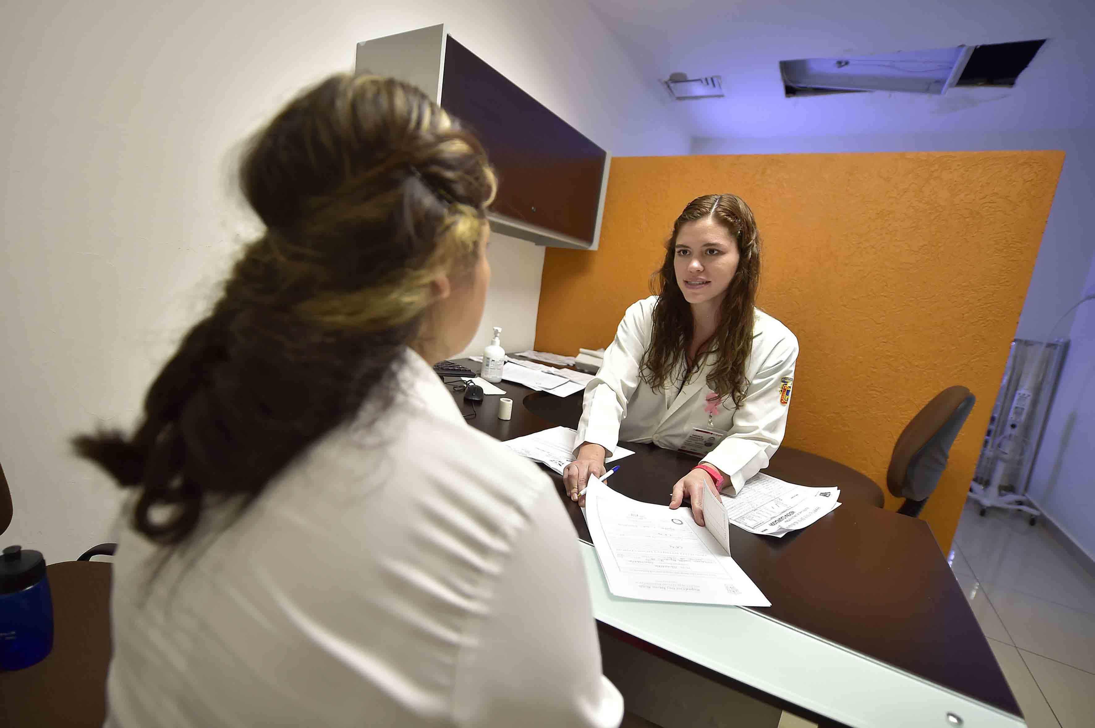 Doctora iniciando cnsulta con encuesta para abrir expediente de la paciente.