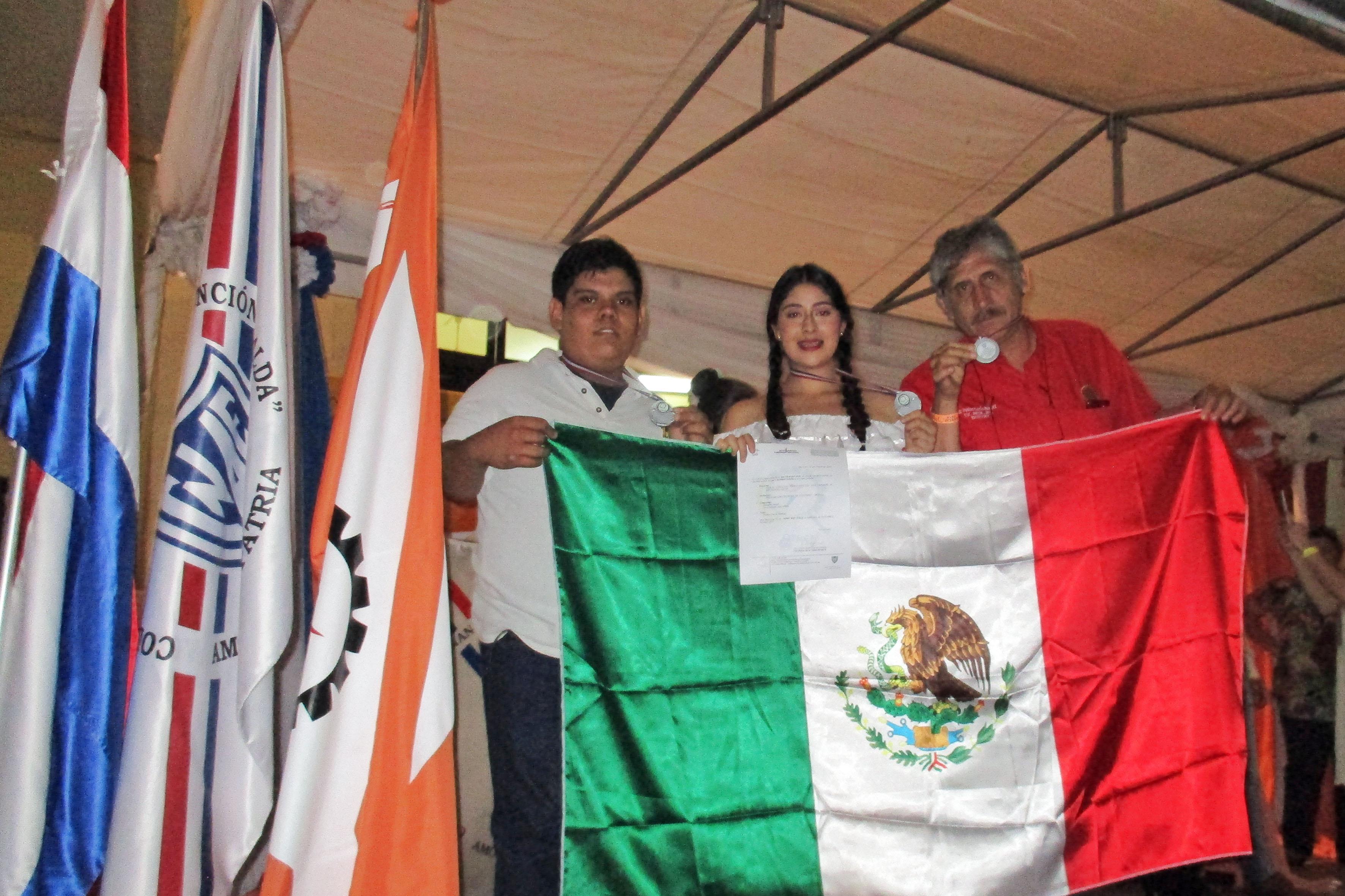 Doctor Paulino García Ramírez y estudiantes ganadores de la Preparatoria de Jocotepec de la UdeG, sosteniendo la bandera de México y mostrando sus medallas