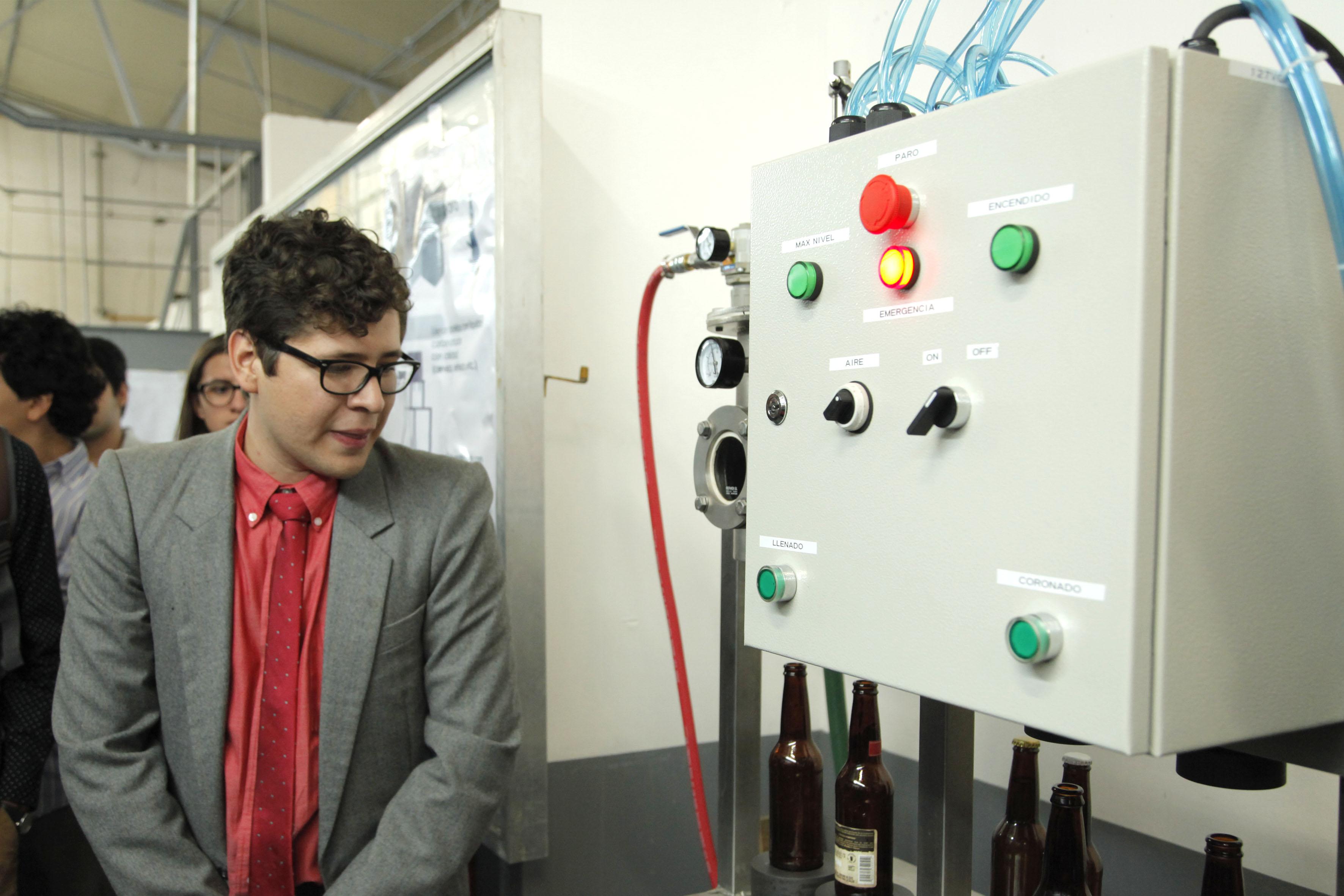 """Estudiante del CUCEI mostrando el prototipo """"Llenadora isobárica para microcervecería"""", durante el Foro Expodime"""