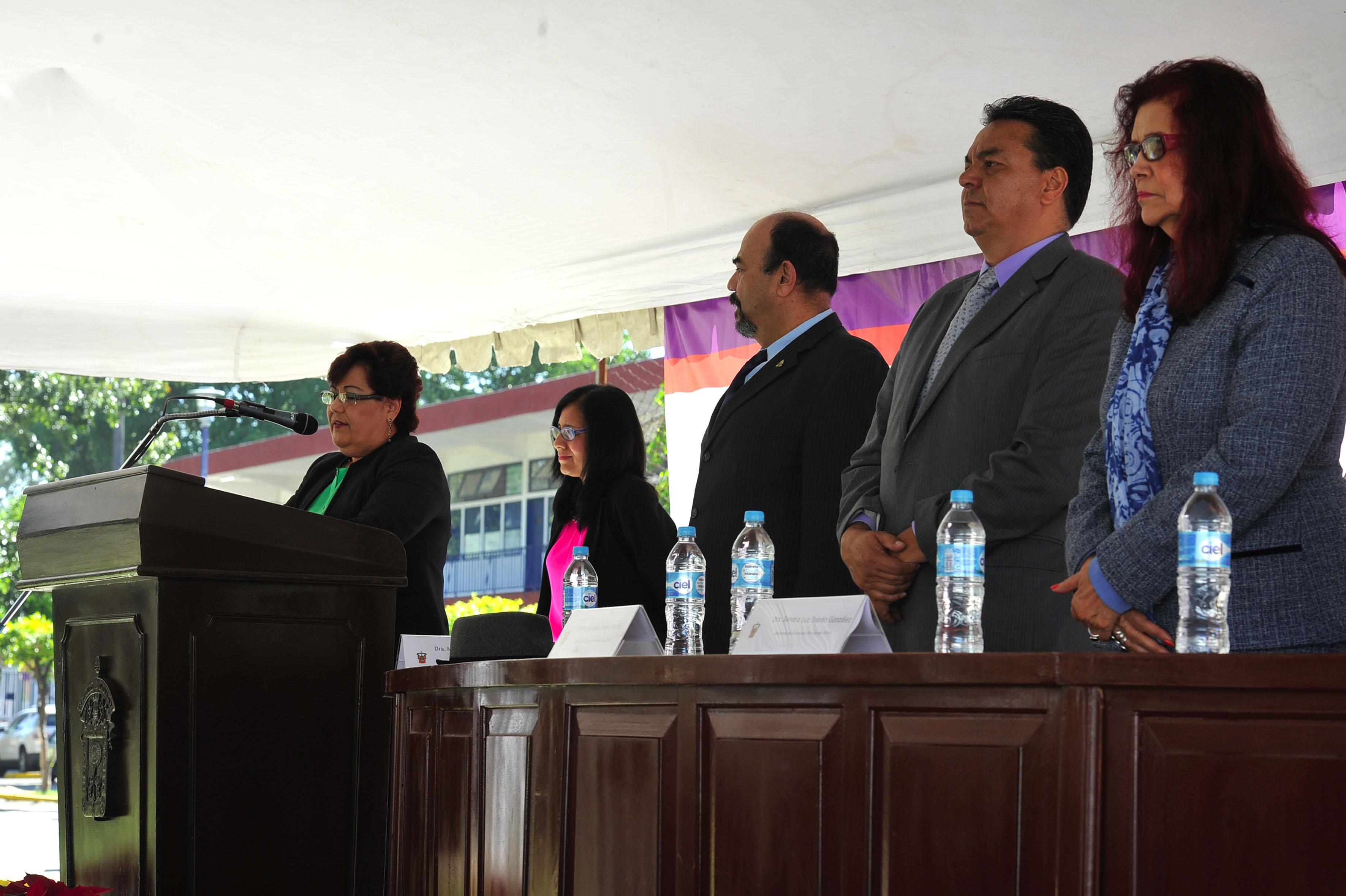 Maestra María de Jesús Haro del Real, coordinadora de Apoyos Académicos del SEMS, con micrófono en podium haciendo uso de la palabra para declarar inagurado los trabajos de la Feria de Innovación Expolitec 2016.