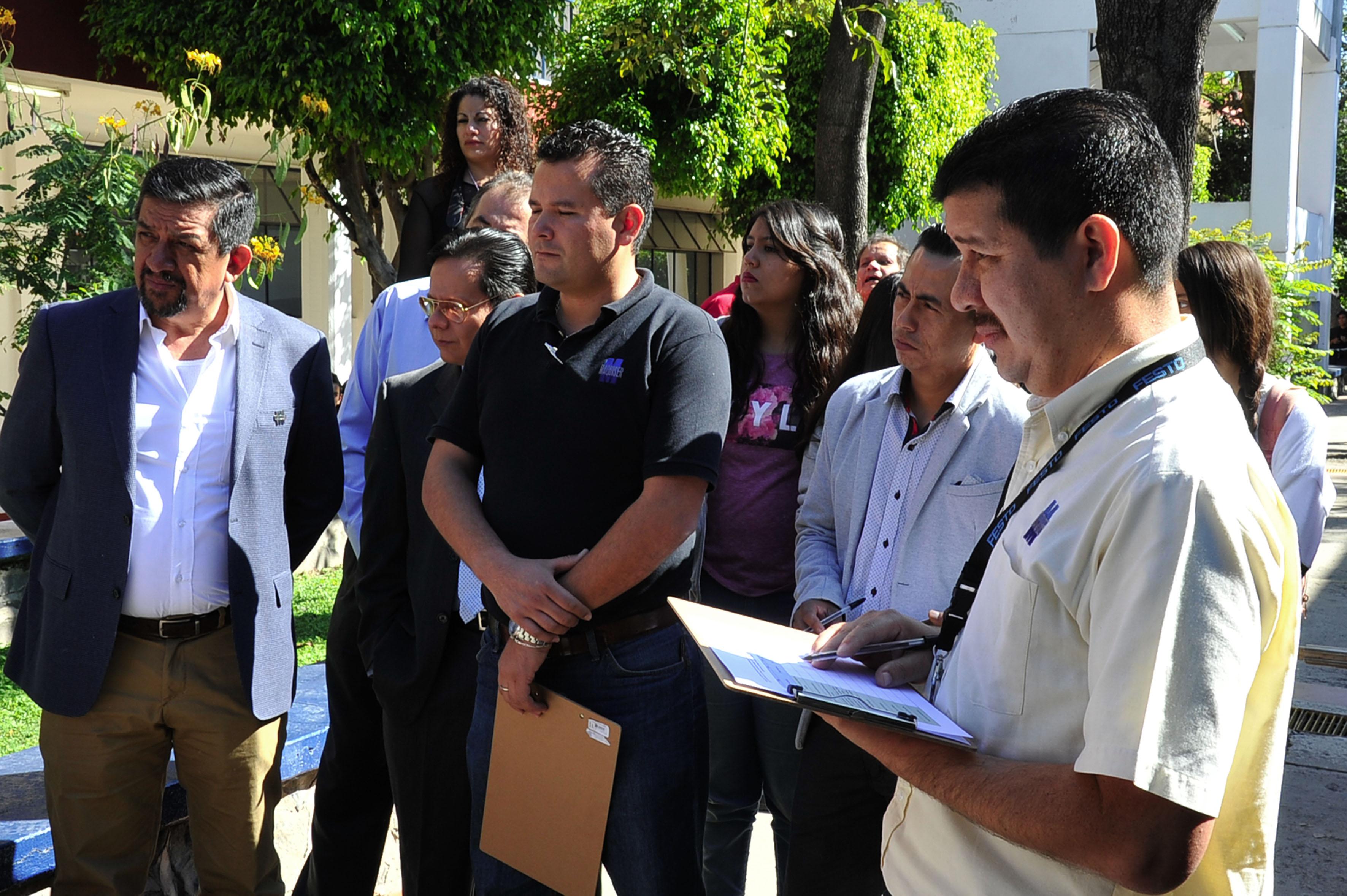 Publico asistente a la Feria de innovación Expolitec 2016, entre ellos representantes de empresas y emprendedores, observando los trabajos exhibidos en la escuela politécnica de la UdeG.