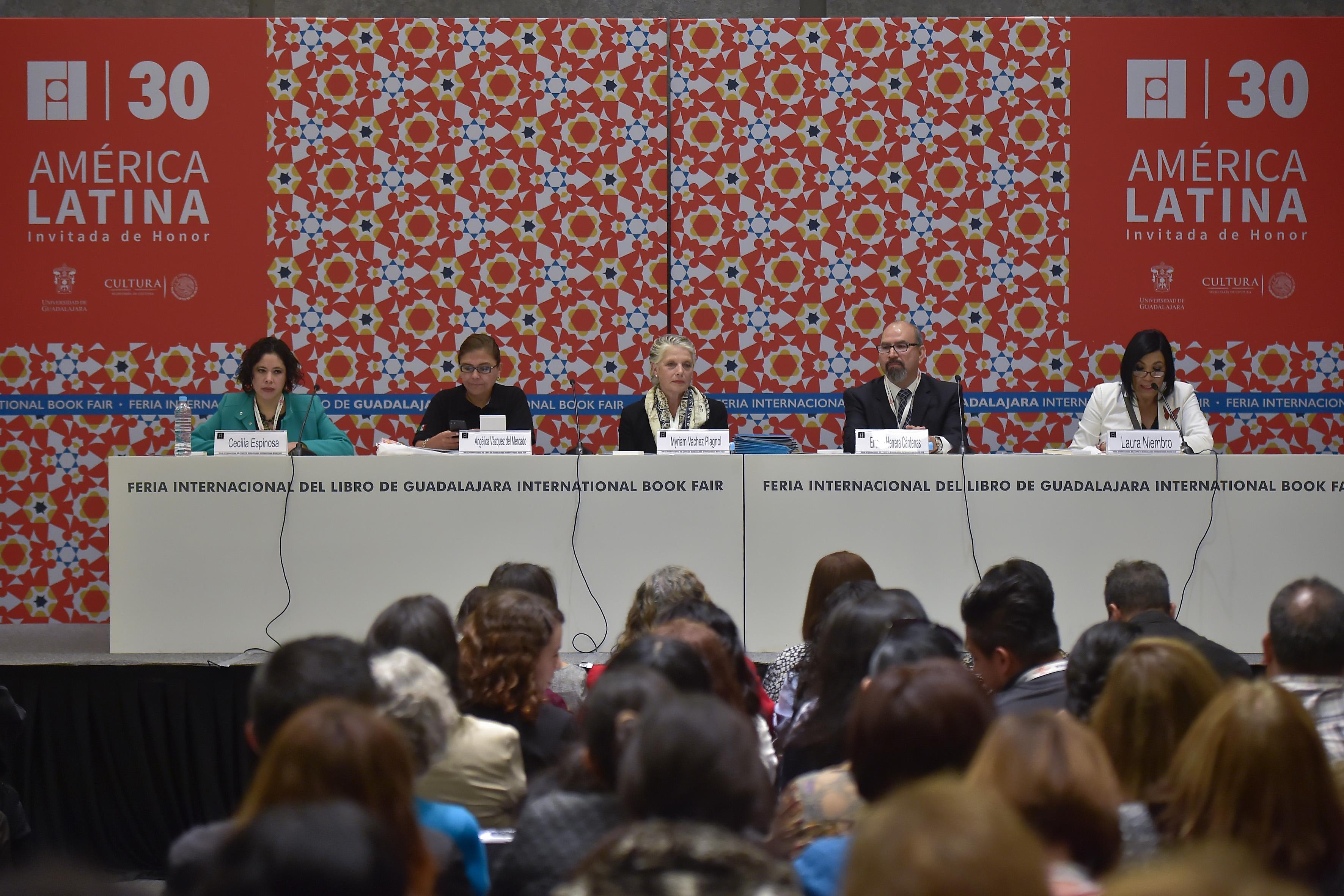 Laura Niembro, directora de Contenidos de la FIL, con micrófono en mesa del panel, haciendo uso de la palabra.