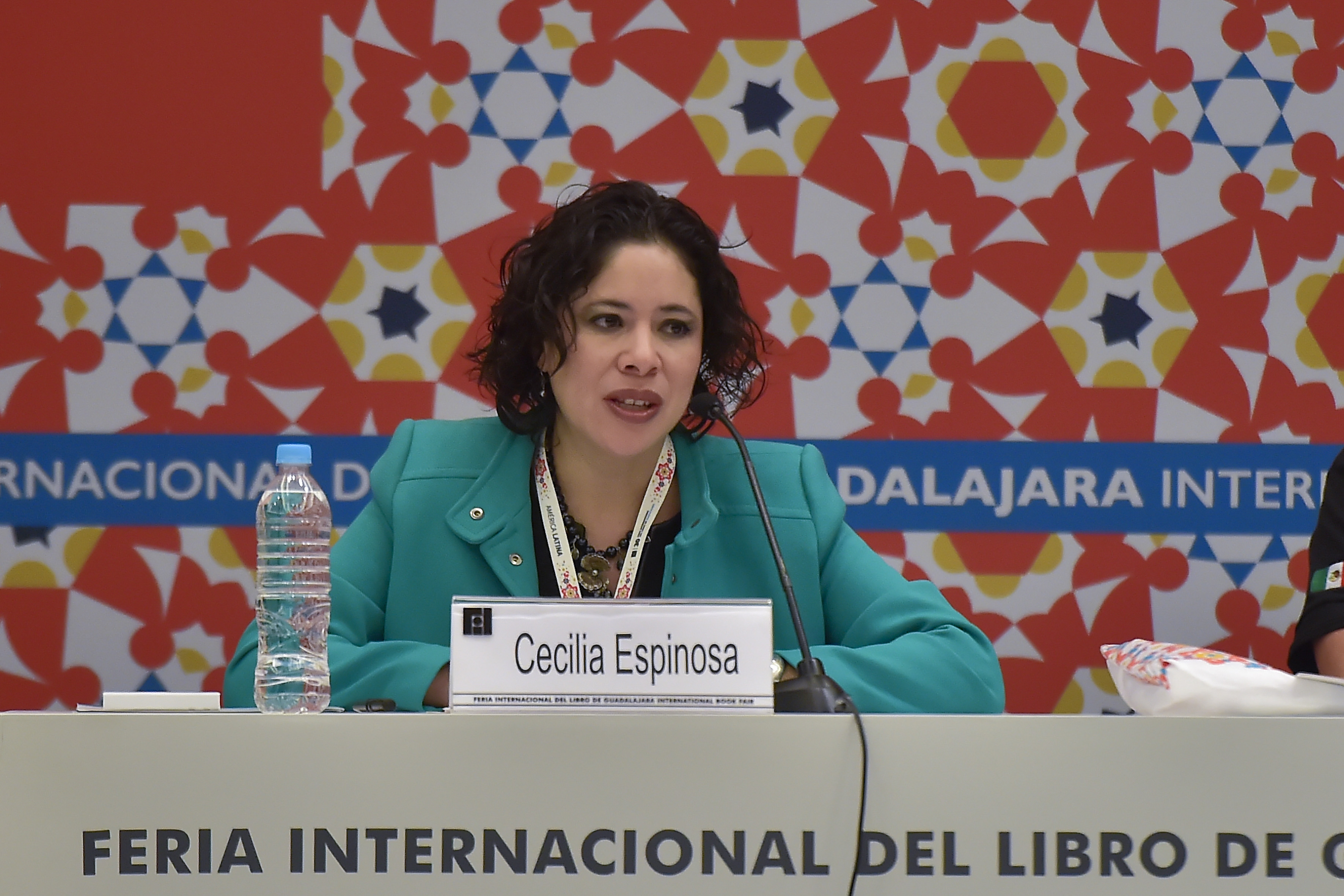 Cecilia Espinoza, directora de la Fundación SM y quien auspicia el programa de promoción de la lectura, con micrófono en mesa del panel, haciendo uso de la palabra.